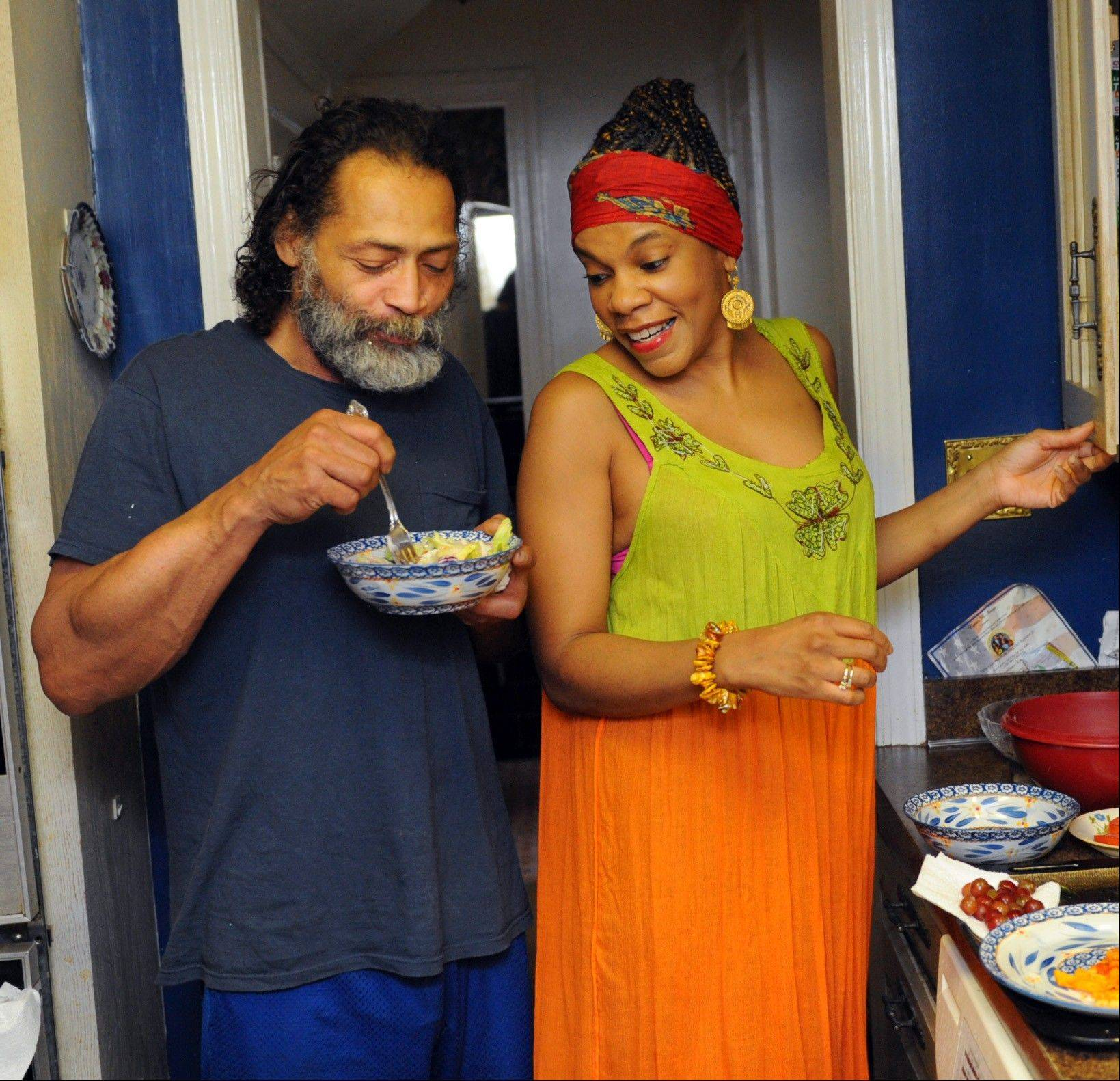 Obesity researchers are studying thin people for clues about hunger. Marlon Adams eats a salad while his fiancee, Maureen Michael, prepares dinner for her mother.