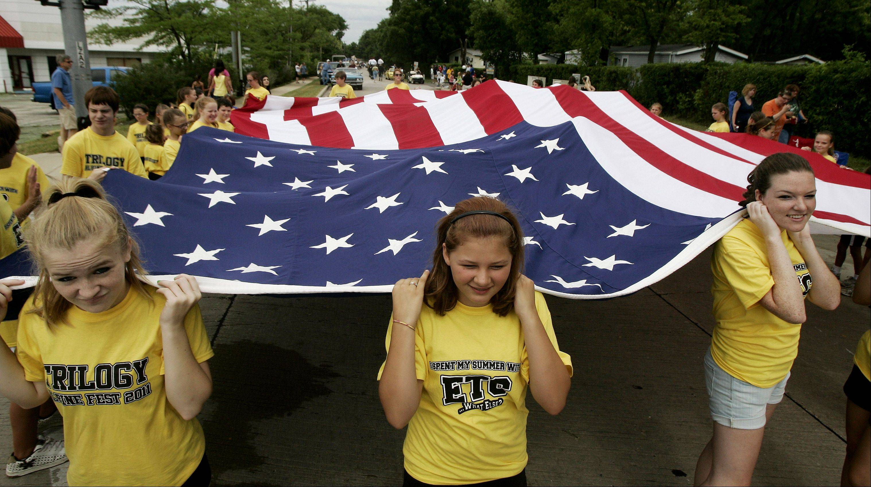 Members of Trilogy Dance carry a large American flag during the Lake Zurich Alpine Festival parade.