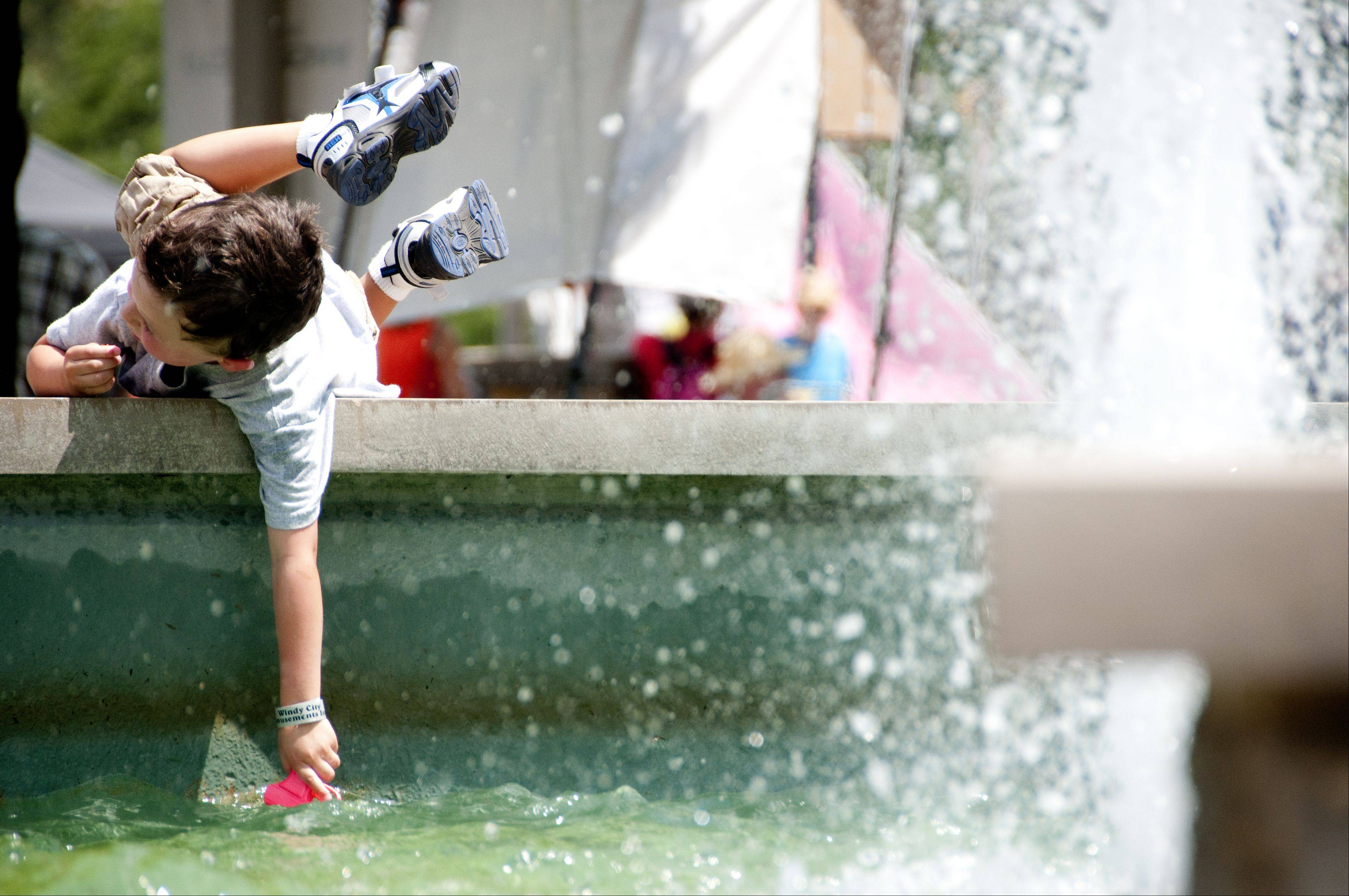 Andrew Dellabella, 4, of Geneva, fills a water pistol in a fountain Sunday at the Batavia Riverwalk.