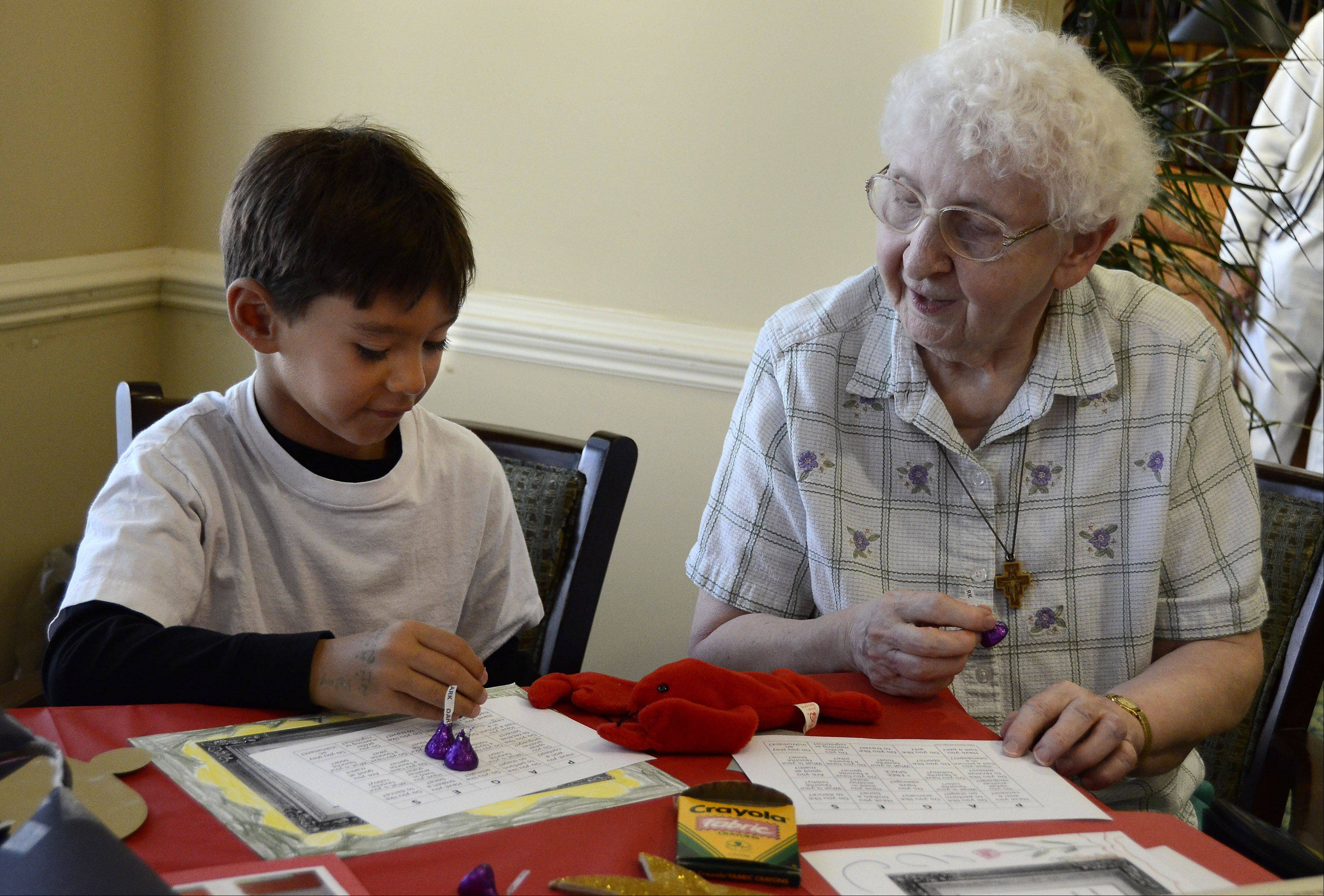Lucas Conwell, 7, and Sister Barbara Koza play Bingo together at the Clare Oaks Retirement Community. They met through Pages Across Ages, an intergenerational reading and writing exchange through the Bartlett Public Library.