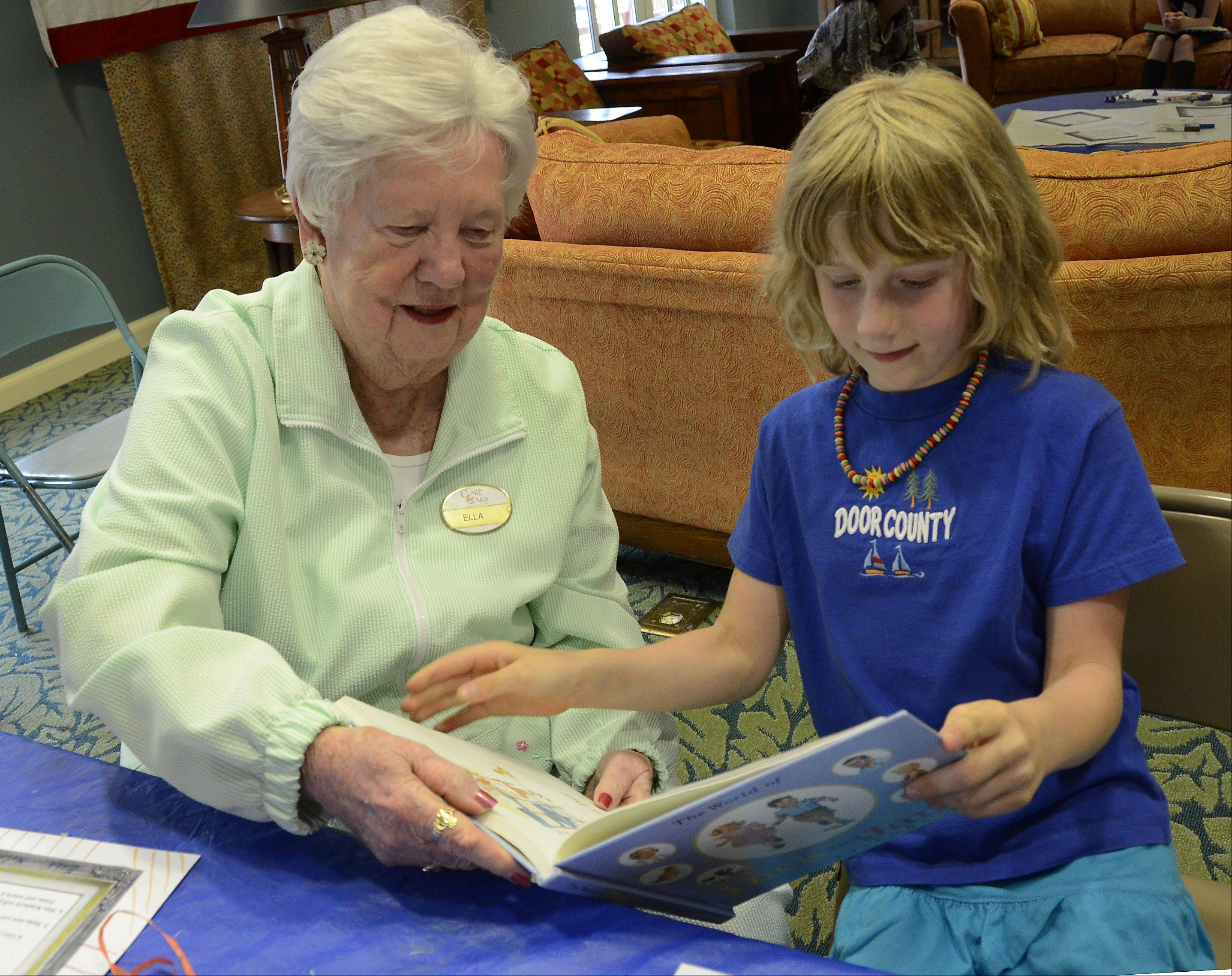 Meeting for the first time, former teacher Ella McCall and Sarah Leardi, 7, look at a book that McCall won at the meet and greet at Clare Oaks Retirement Community. They are participants in the Pages Across Ages intergenerational reading and writing exchange through the Bartlett Public Library.