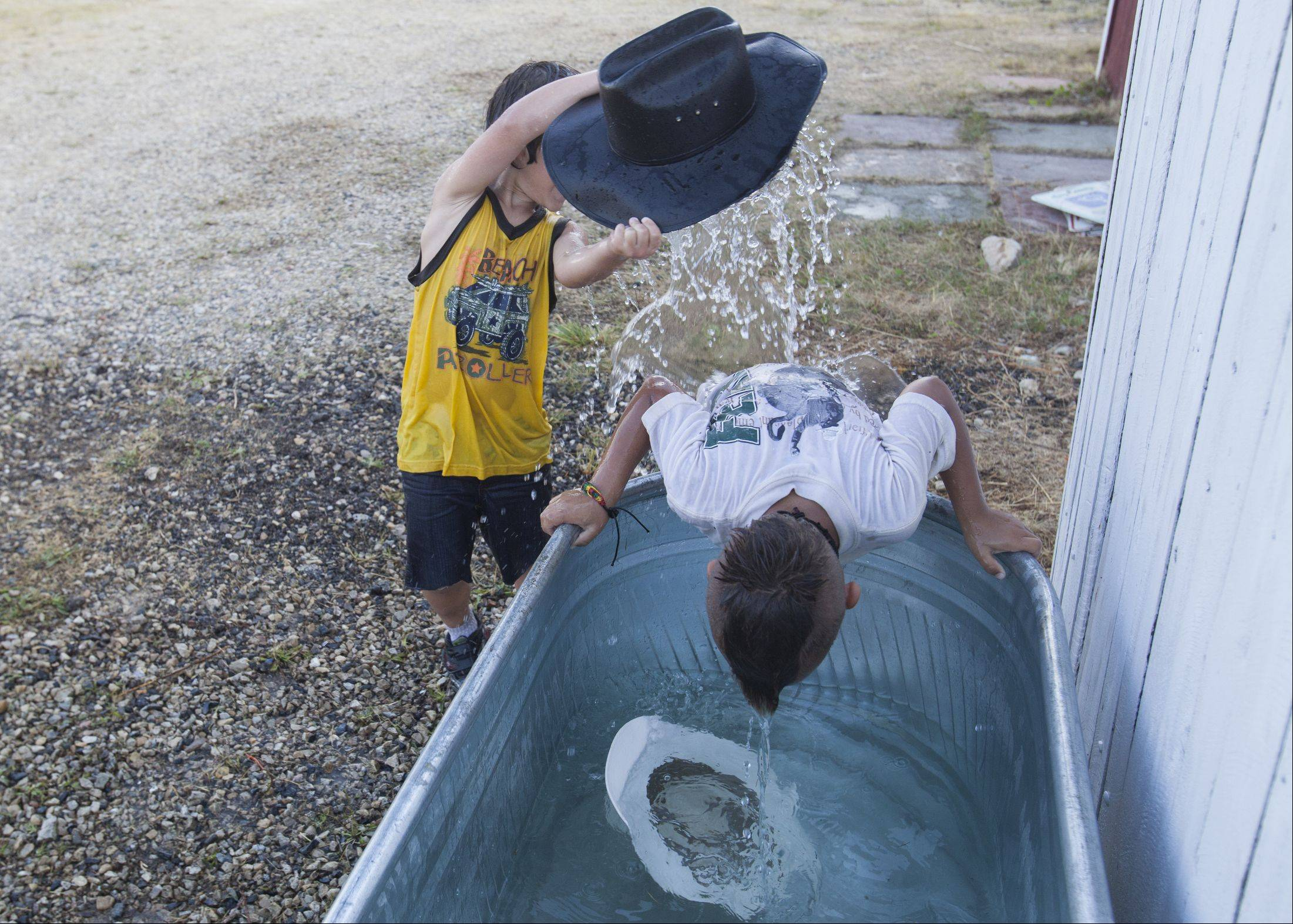 Anthony DeTomari, 7, dumps a hat of water on Luka Phillips, 6, both of Wauconda, as they try to beat the heat Sunday during the 49th IPRA Championship Rodeo in Wauconda.