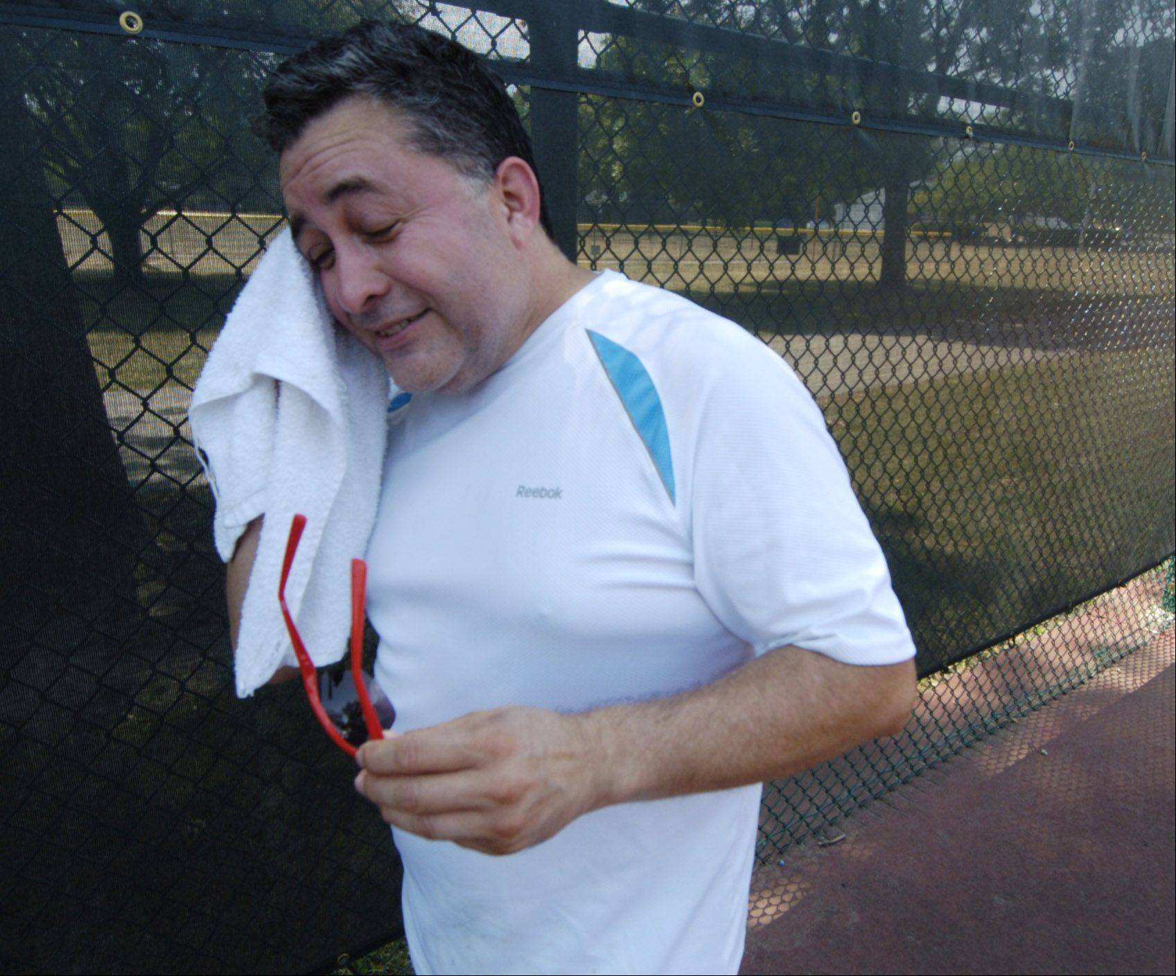 Honorio Vega, who lives in Highland Park and works in Des Plaines, wipes his forehead after playing tennis with a co-worker during the noon hour at Lions Park in Mount Prospect Friday.