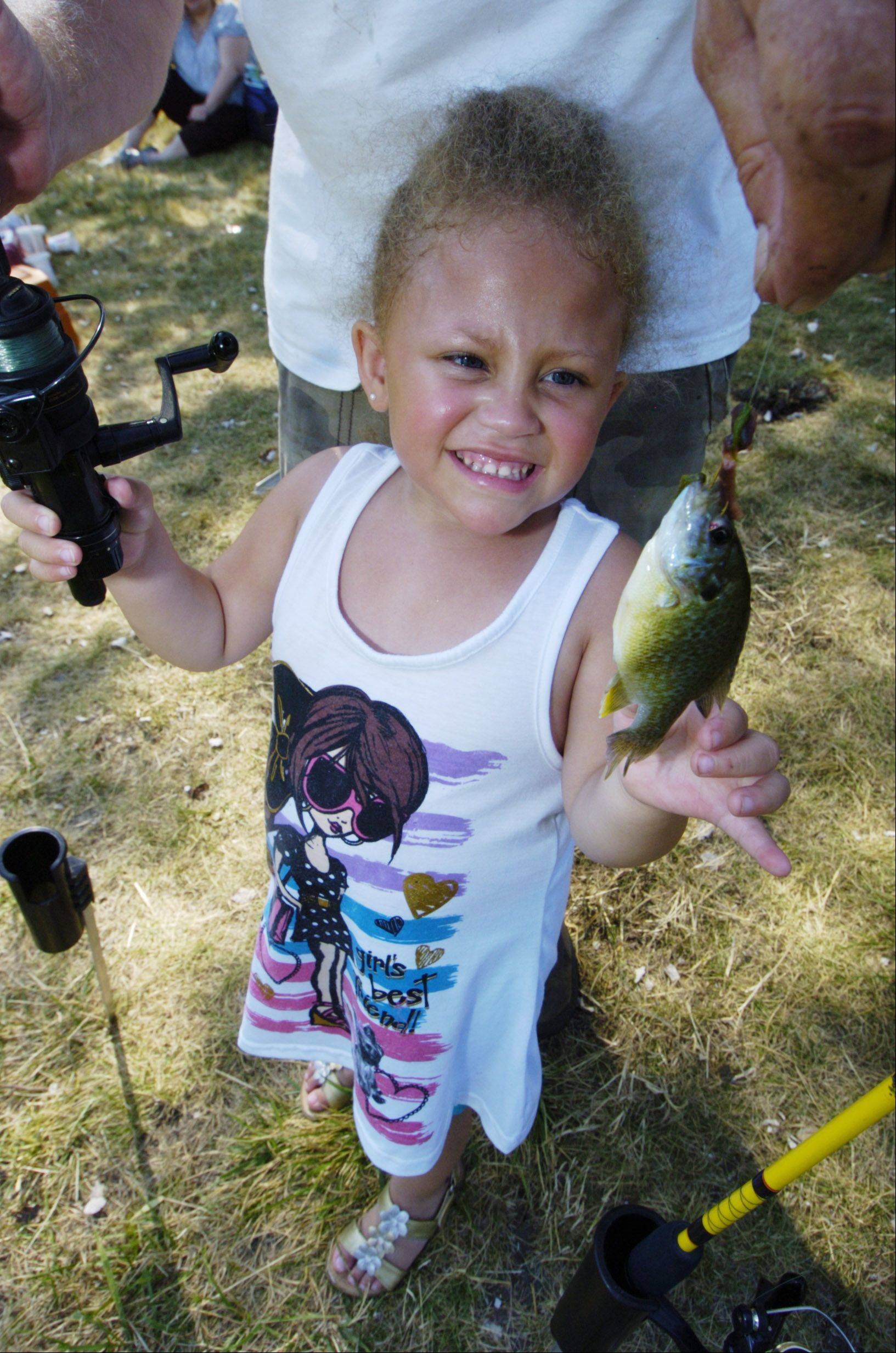 "Bella Adams, 4, of Winthrop Harbor catches a ""small fry"" during Saturday's fishing derby for kids at Maurice Noll Park in Mundelein."