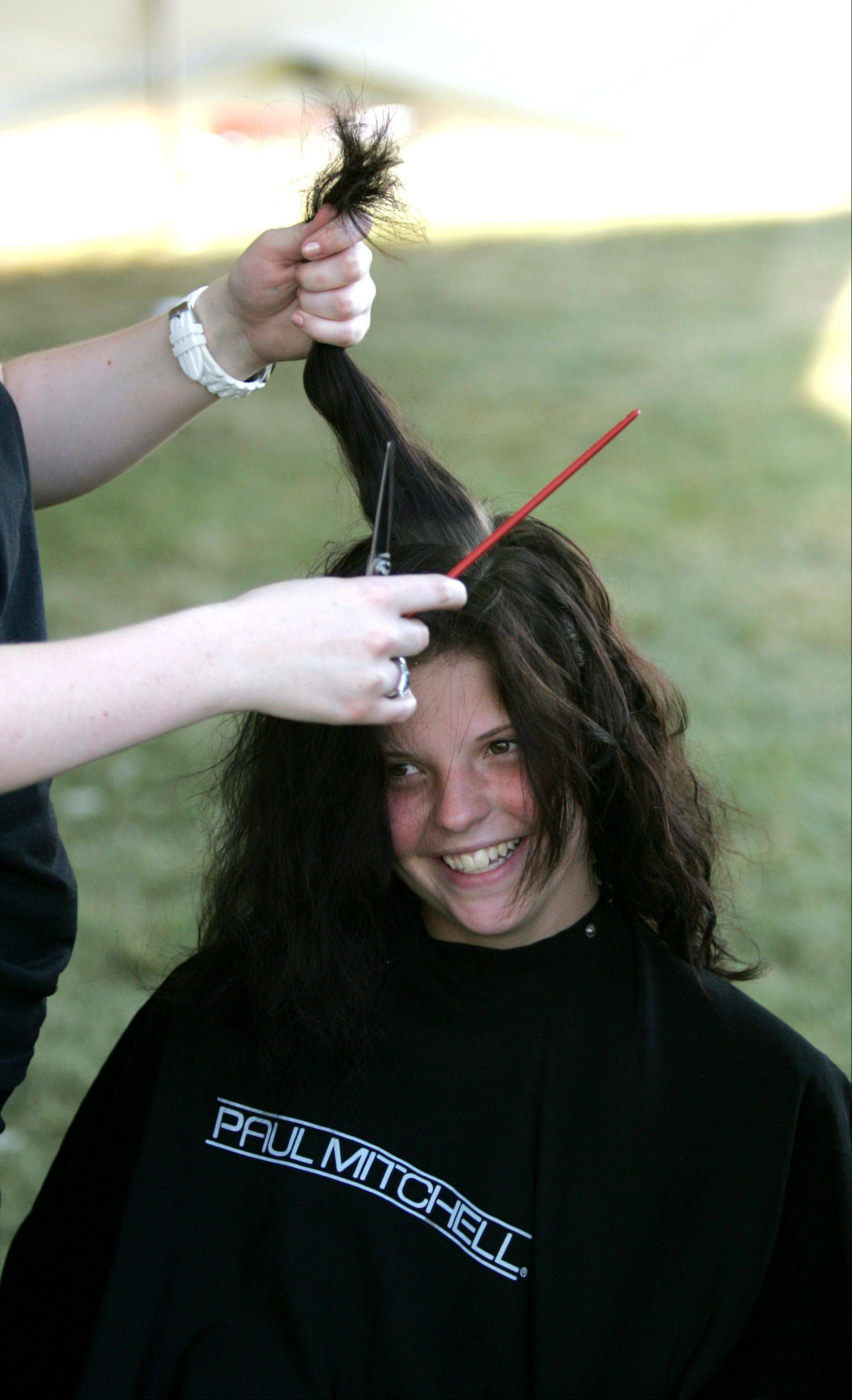 Britney Culp gets her hair cut by Paul Mitchell the School Chicago as part of a St. Baldricks fundraiser at the Taste of Lombard in Madison Meadow Park. Paul Mitchell the School Chicago raised over $88,000 for charity last year.