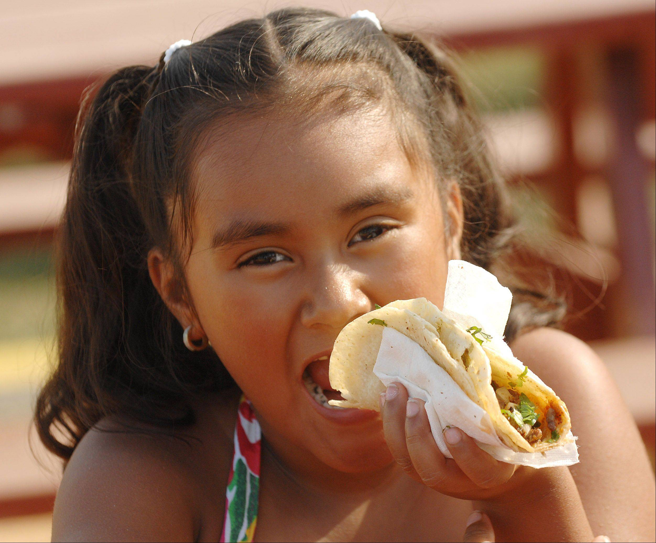 Fabiola Cruz, 6, of West Chicago enjoys a taco during Railroad Days in West Chicago Thursday. Today was the first day of this fest that runs through the weekend. The fest offers food games and fun for all ages.