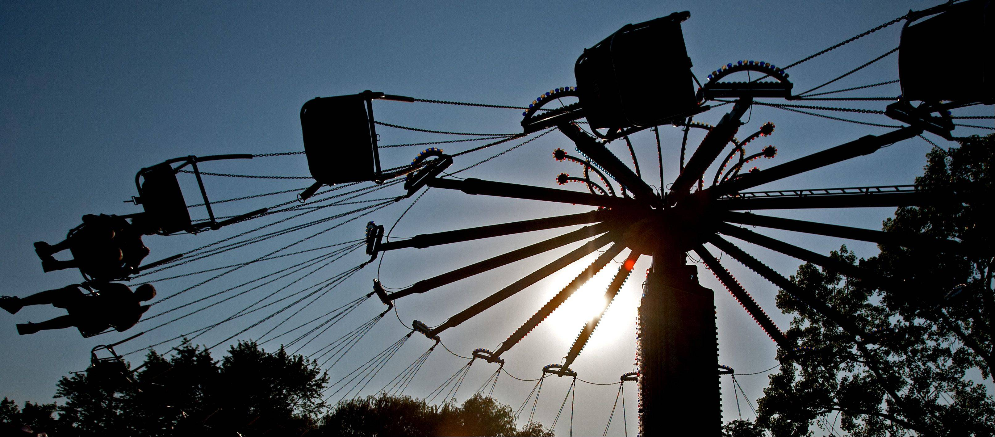 Several carnival riders fly through blistering heat, during the Taste of Lombard at Madison Meadow Park.