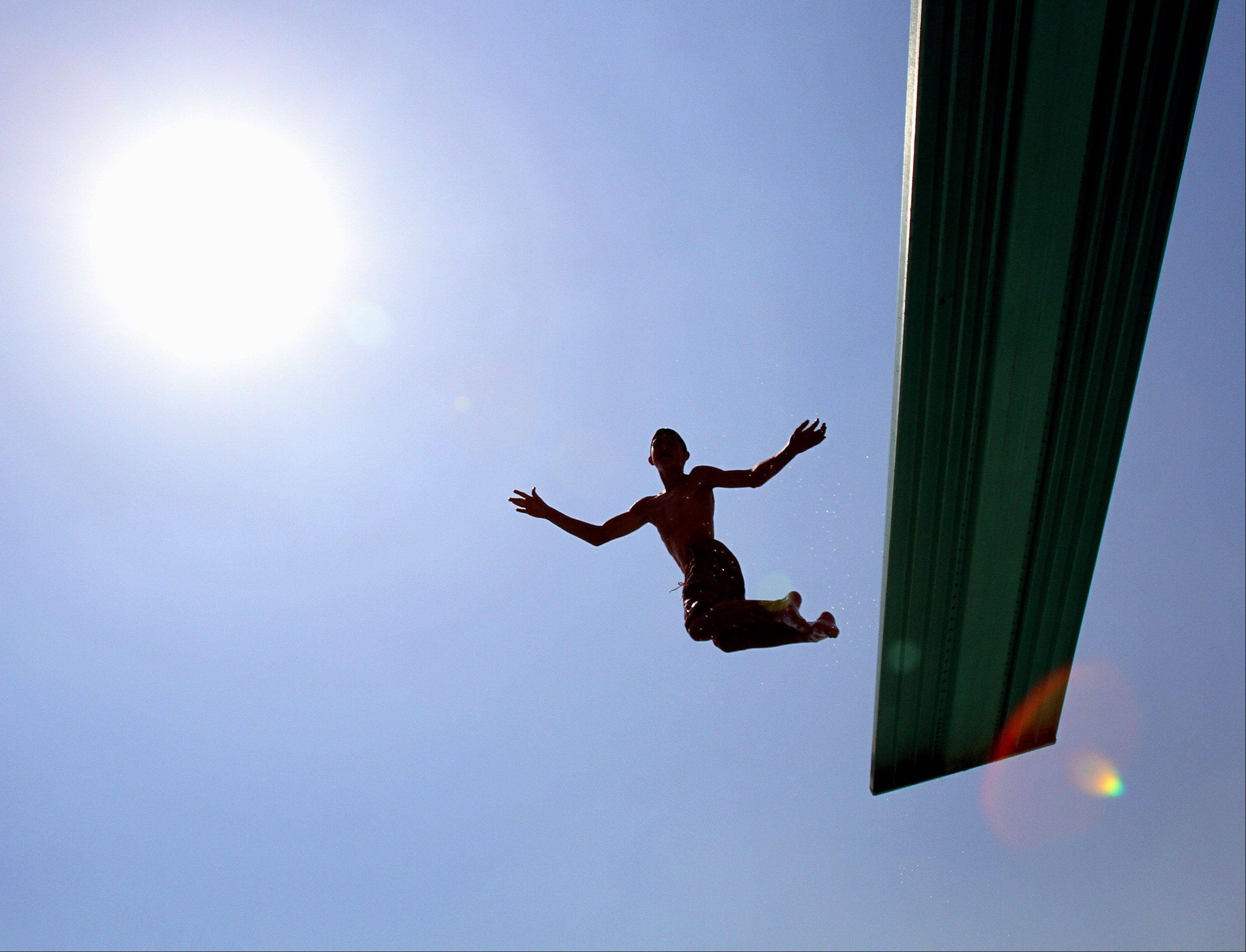 Jake Wenz, 12 of Naperville, jumps off the high board at Centennial Beach in Naperville on Friday.