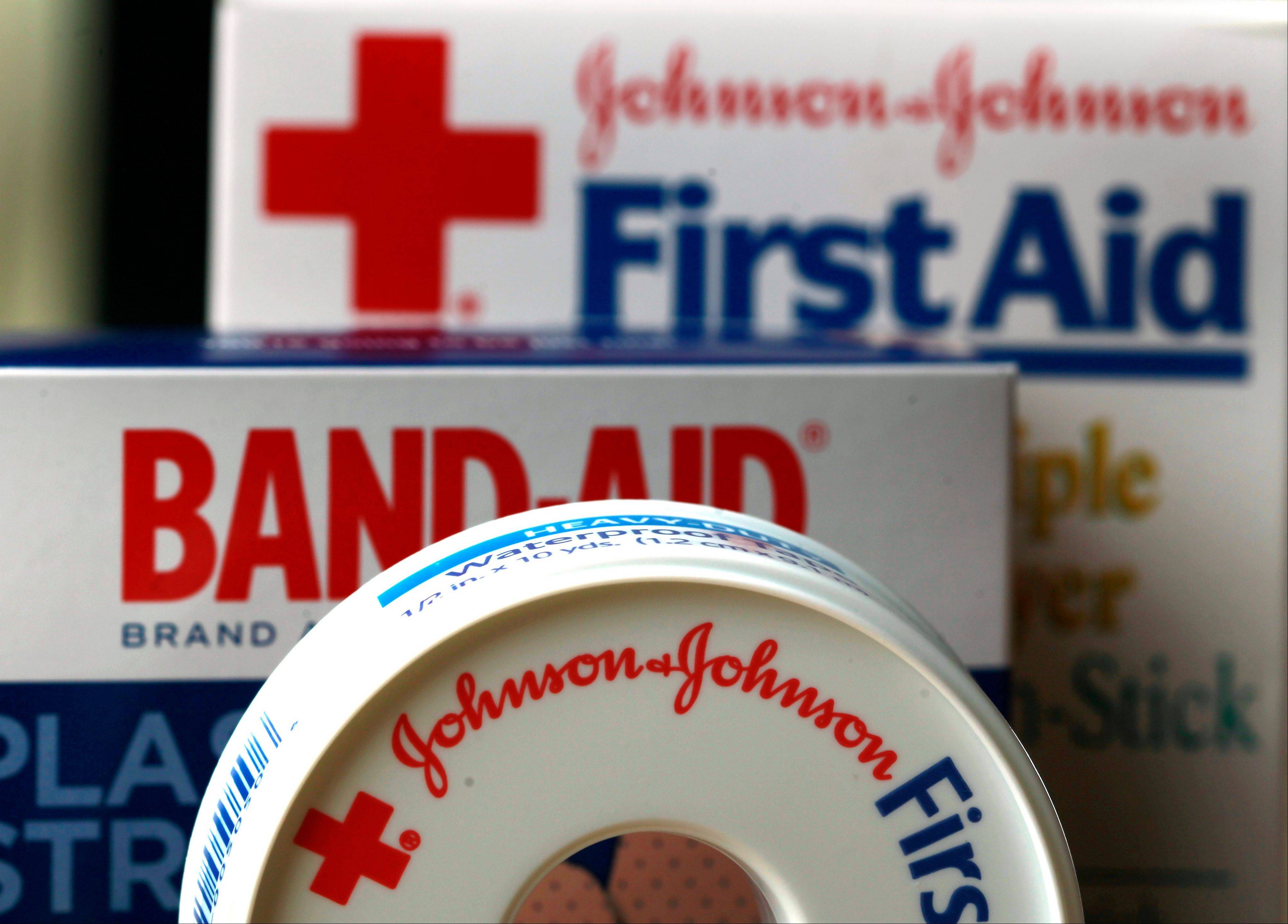 Johnson & Johnson, a health care giant that is struggling with tougher market conditions, ongoing manufacturing problems and other issues, lowered its profit forecast for the year after posting second-quarter net income that dropped by half. The maker of Band-Aids, medical devices and prescription drugs whose iconic image has been tarnished by legal and manufacturing lapses on Tuesday, July 17, 2012 noted some positive signs.