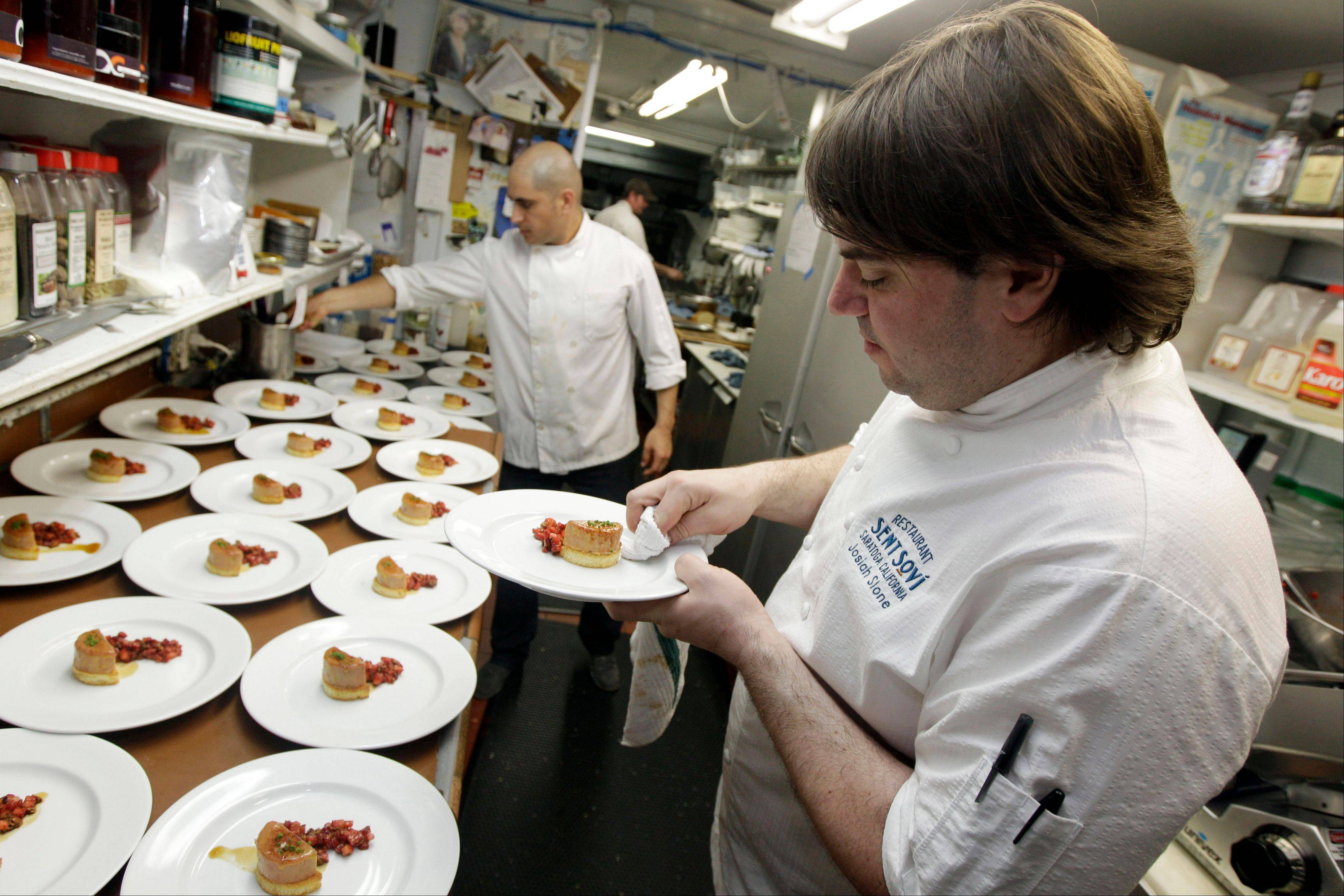 Chef and owner Josiah Slone, right, prepares a foie gras dish at the Sent Sovi restaurant in Saratoga, Calif.