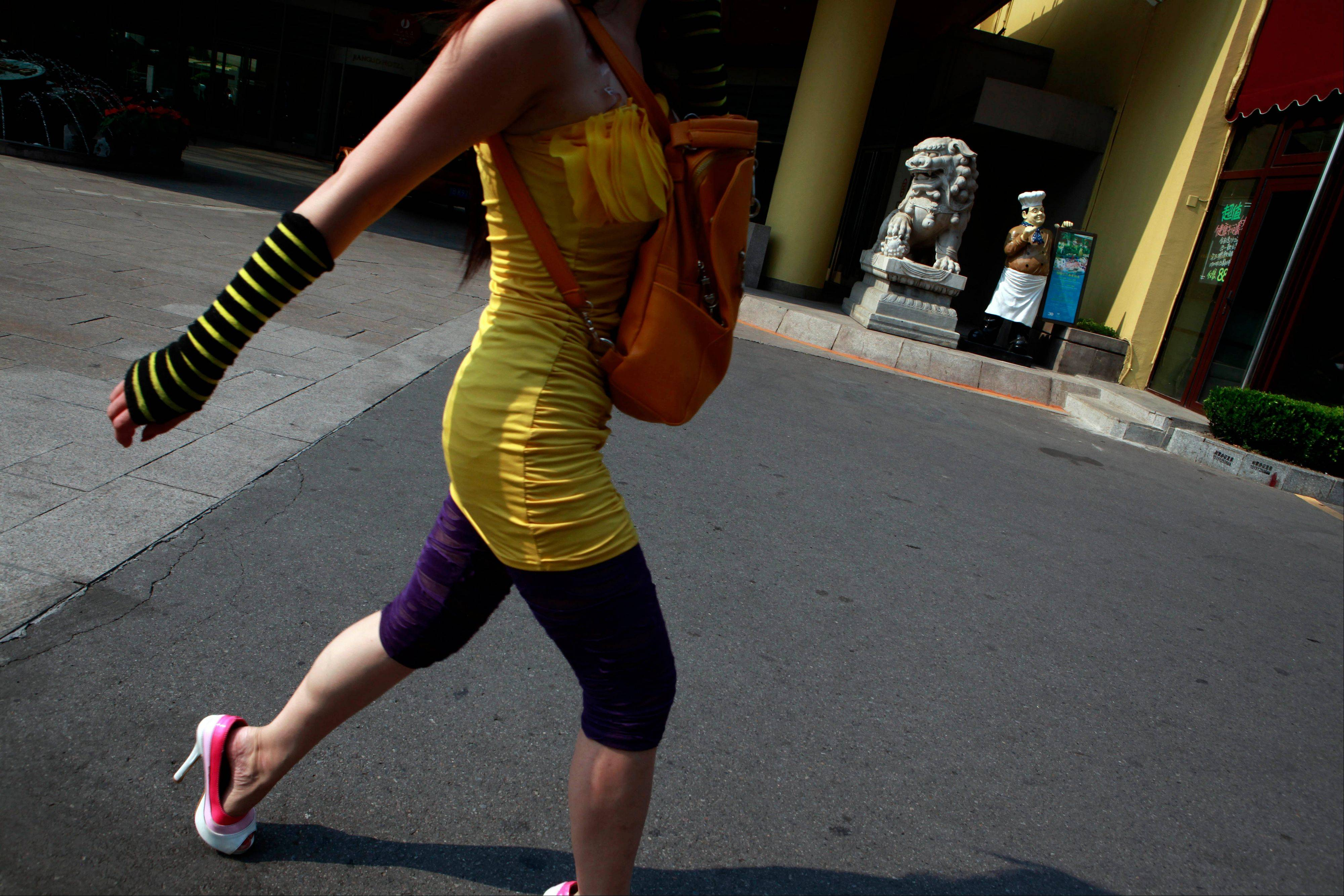 A Chinese woman walks past a hotel in Beijing, China, Monday.