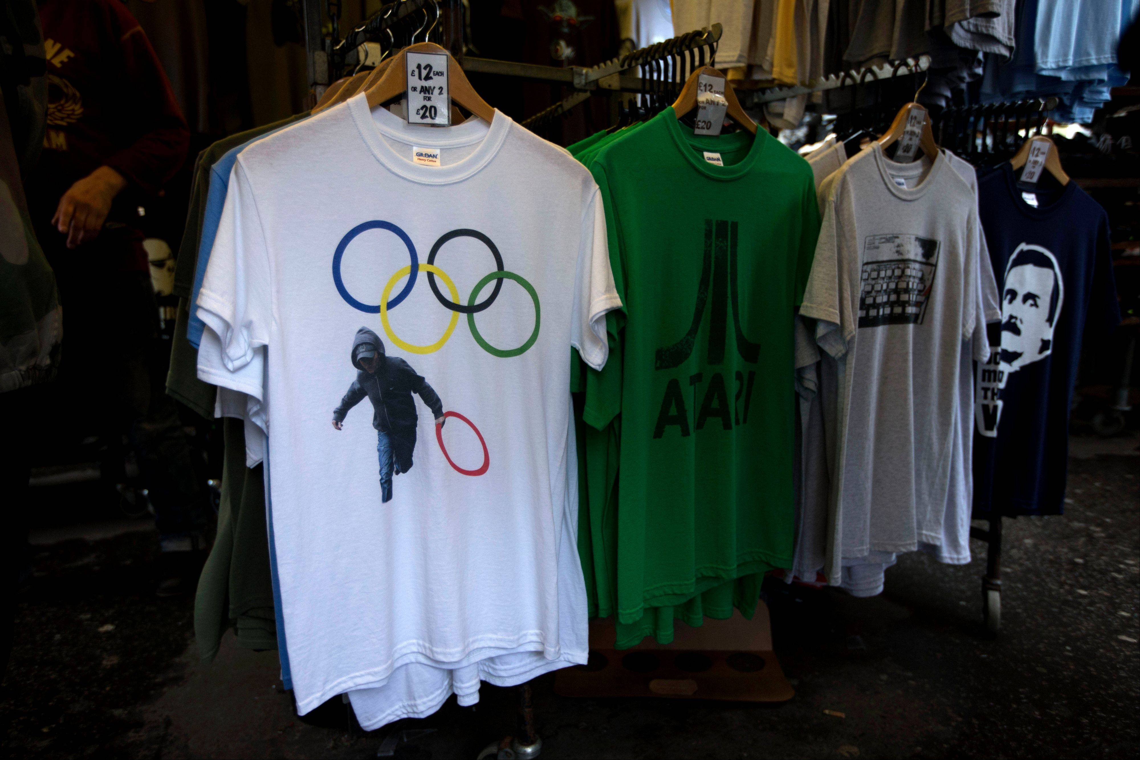 In this photo taken Monday, July 16, 2012, a t-shirt depicting a rioter holding an Olympic ring is displayed on sale in a London market. The guardians of the games are vigilant about protecting the integrity - and the commercial clout - of the Olympic brand. But even they can�t stop the irreverent spirit of artists and craftspeople, who have responded to the games with a cheeky mix of celebration, skepticism and satire.