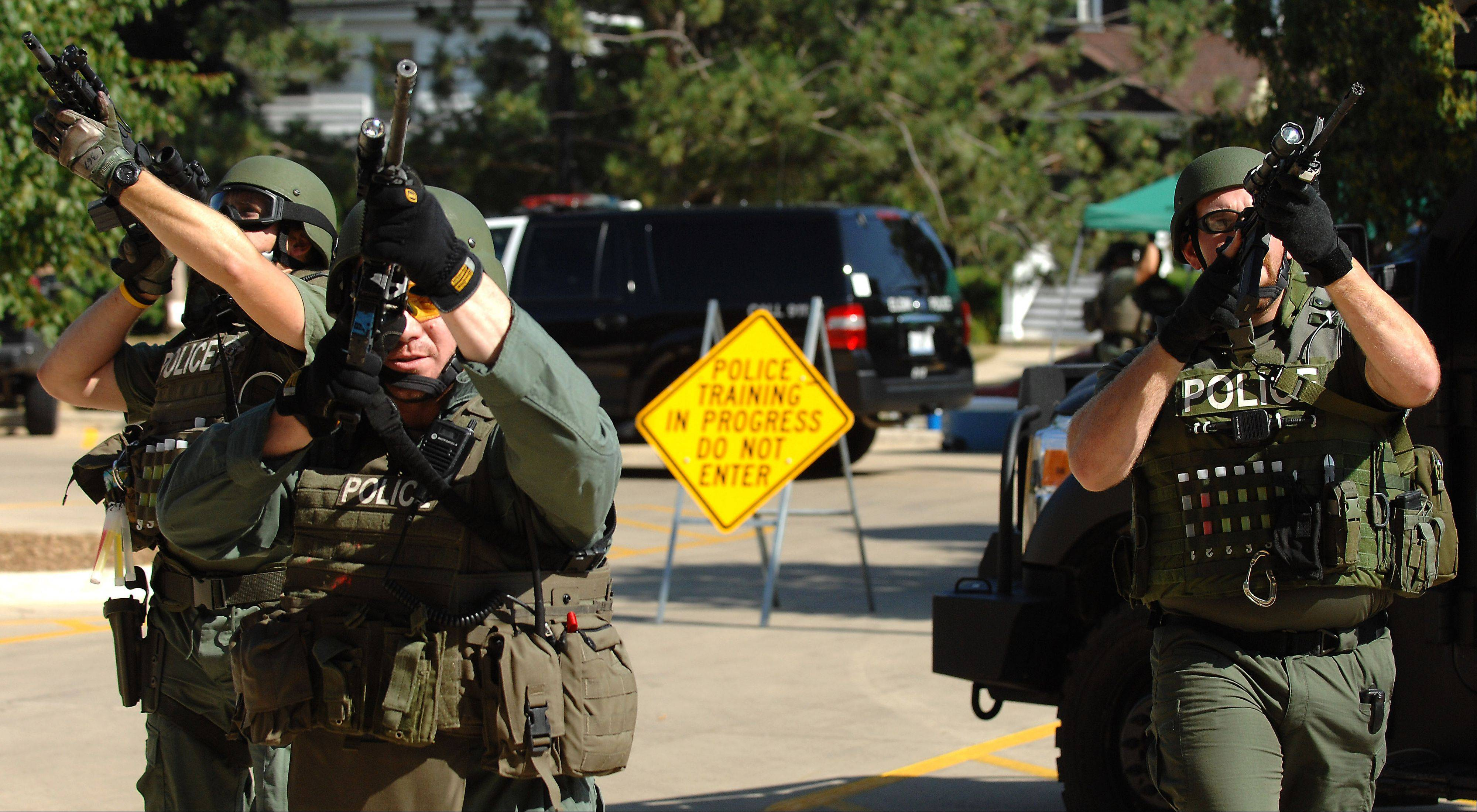 Elgin SWAT team members approach Gifford Street High School in Elgin during a training exercise Tuesday. The scenario involved a call about multiple school shooters.