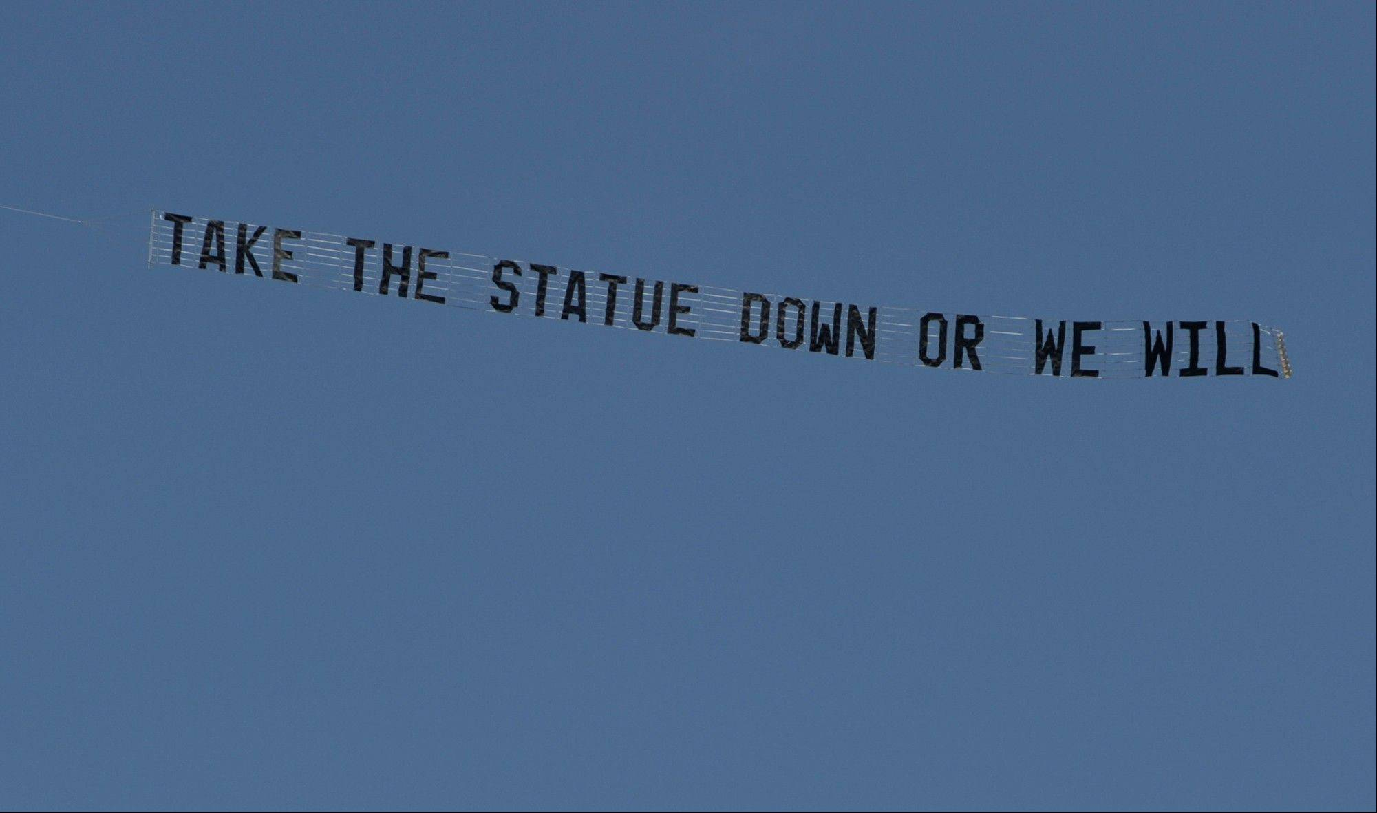 "A plane flying over the Penn State University campus Tuesday pulls a banner reading ""Take the statue down or we will."" The Paterno statue outside Beaver Stadium has been a point of much contention. Critics have called for the statue to be taken down after the Freeh report concluded that Paterno was aware of a 1998 allegations against Sandusky — in contrast to his grand jury testimony and an interview given after his firing — and that he was involved in the decision to not report a 2001 incident to the authorities even after his superiors had decided to."