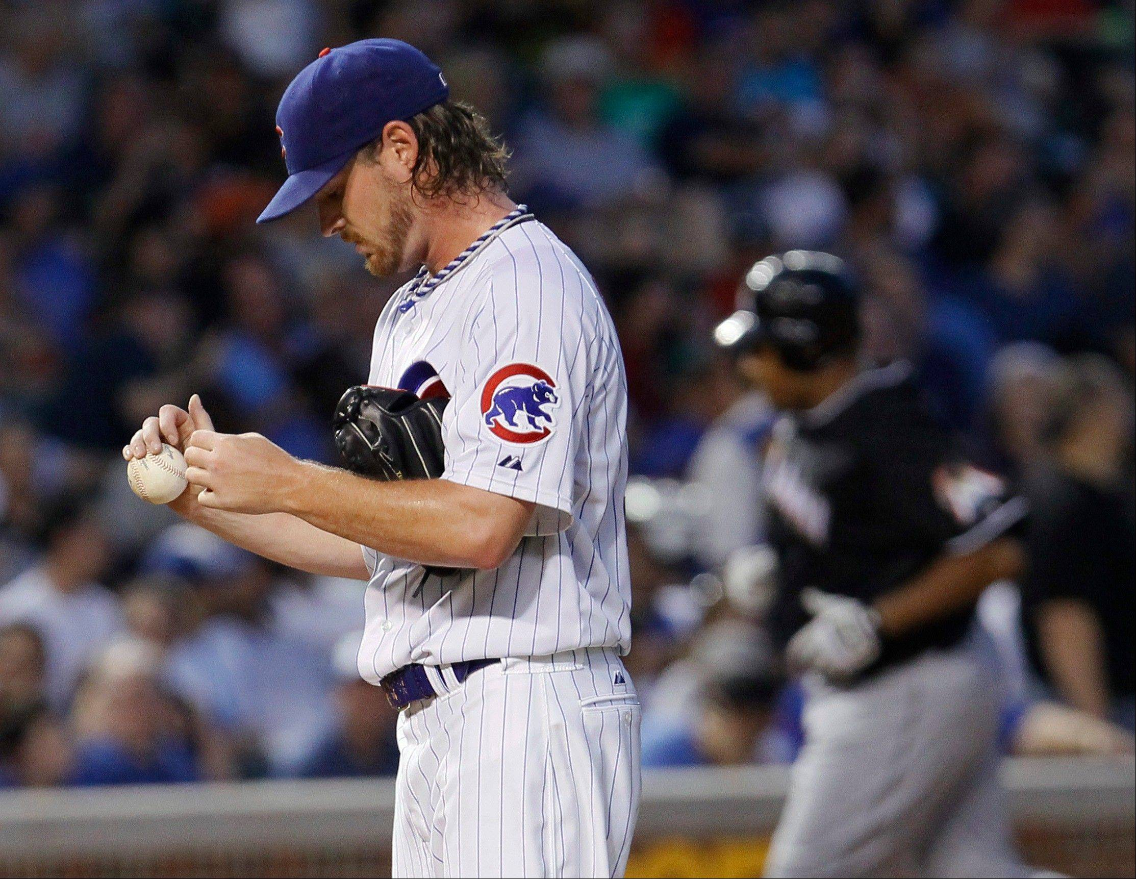 Cubs starting pitcher Travis Wood returns to the mound Tuesday after giving up a grand slam to the Miami Marlins' Carlos Lee, background, during the fifth inning at Wrigley Field.