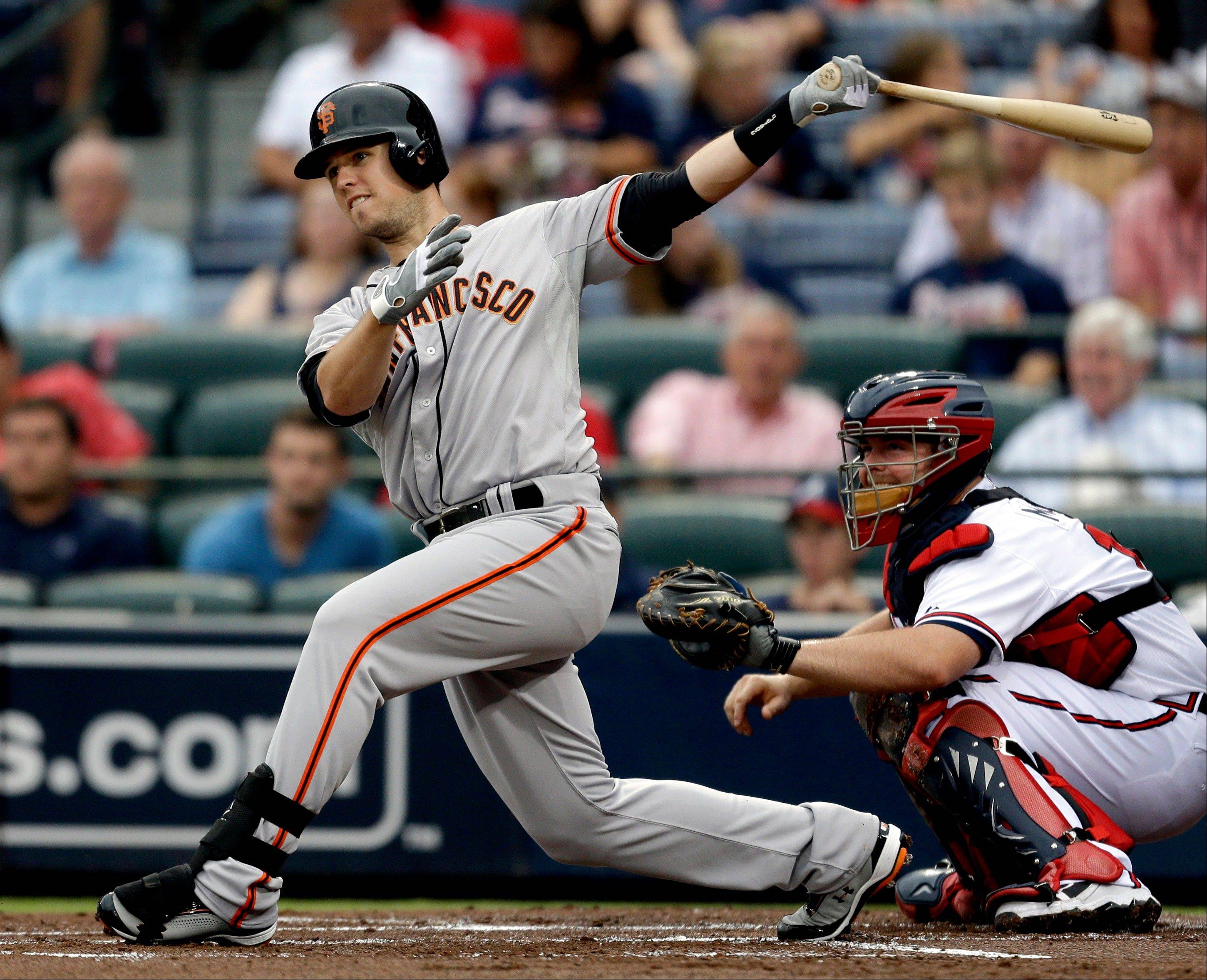 San Francisco Giants catcher Buster Posey, left, doubles to score teammate Gregor Blanco Tuesday during the first inning against the Atlanta Braves in Atlanta.