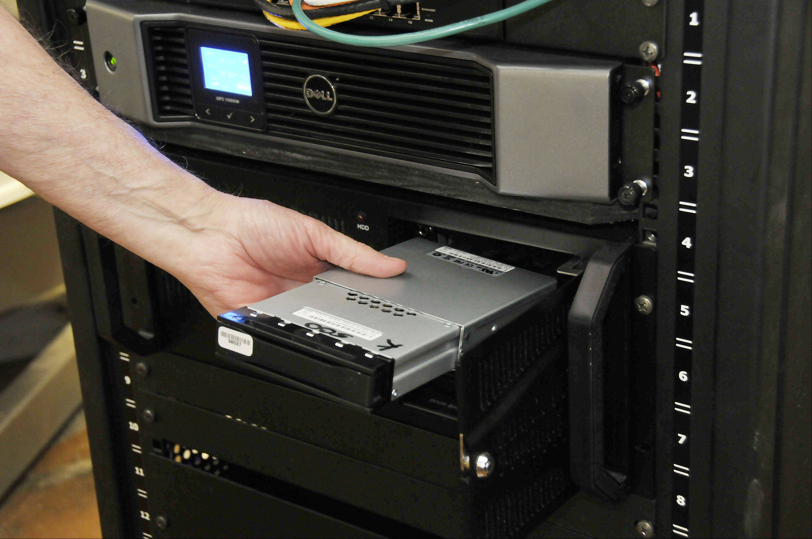 Willis Johnson, owner of Tivoli and Classic Cinema theaters, shows how the digital movies are fed into the back of a new digital projector on a portable hard drive at The Tivoli in Downers Grove. Movies can also be directly downloaded into the theater's computer system via a satellite dish on the roof.