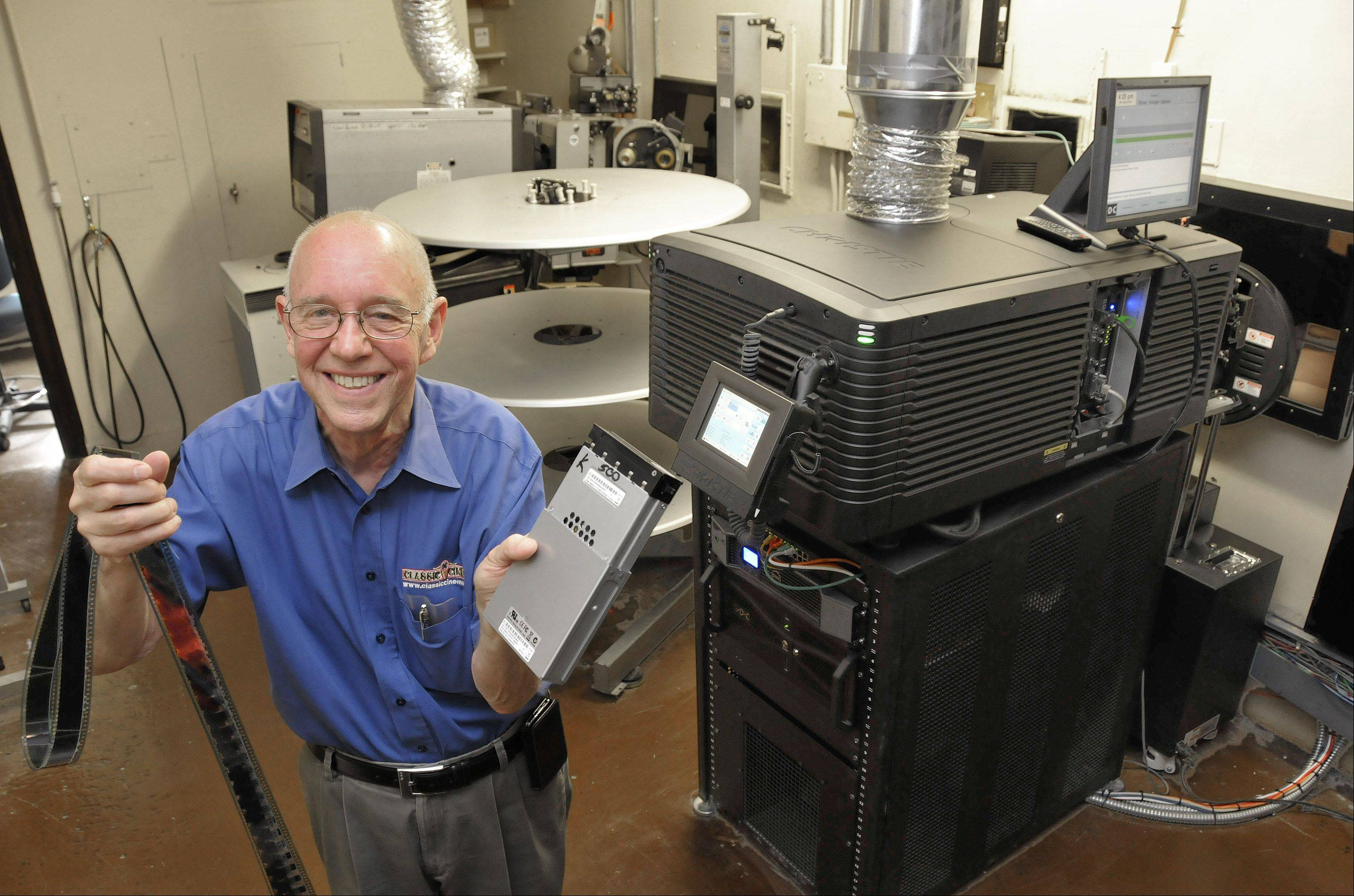Owner Willis Johnson, in the projection booth at the Tivoli in Downers Grove, holds a traditional 35 mm movie film clip in his right hand and one of the hard drives in his left hand that the digital movies come in now. The hard drive goes in the computer-controlled projector and sound system, in the foreground.
