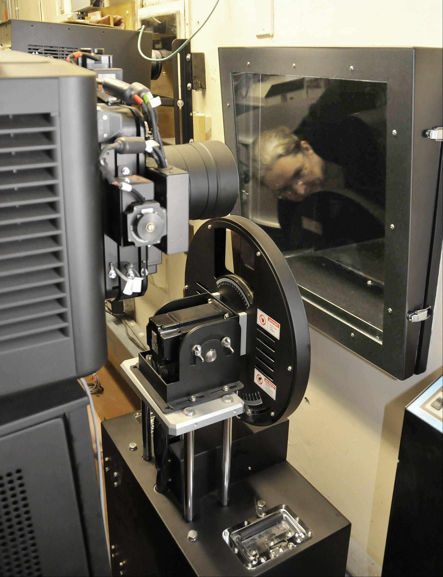 A new projector at The Tivoli in Downers Grove uses no film. In the projection booth, Tivoli General Manager Linda Smith, visible reflected in the glass, moves the round 3-D filter unit into position in front of the digital projector's lens.