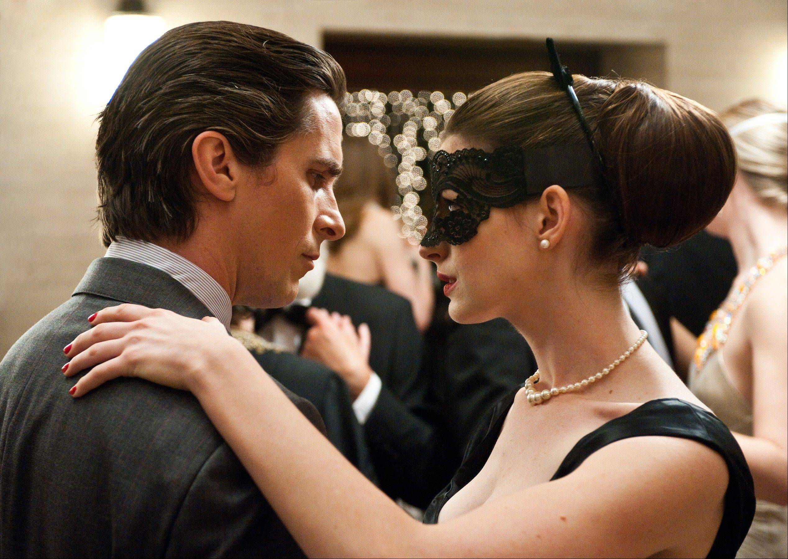 "Bruce Wayne (Christian Bale) becomes intrigued by cat burglar Selina Kyle (Anne Hathaway) in Christopher Nolan's action thriller ""The Dark Knight Rises."""