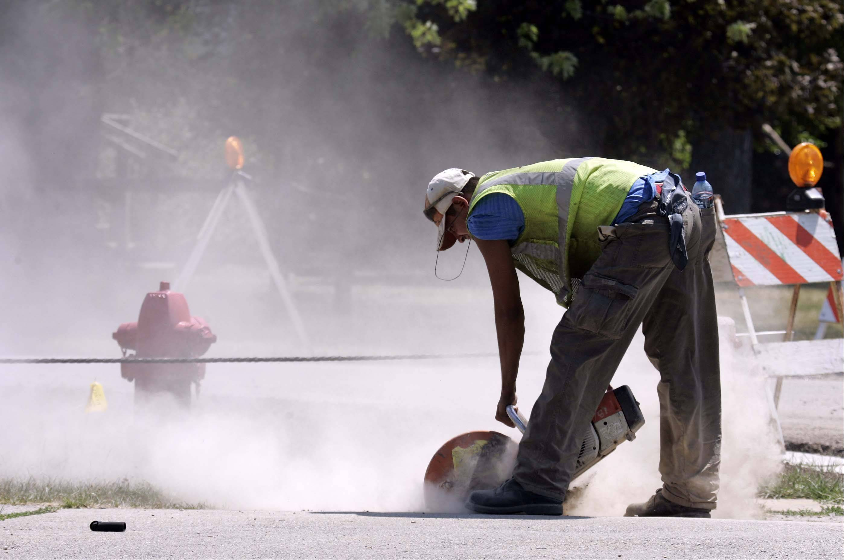 Arturo Garza of Hardin Paving Company paves works in the heat Tuesday in Geneva.