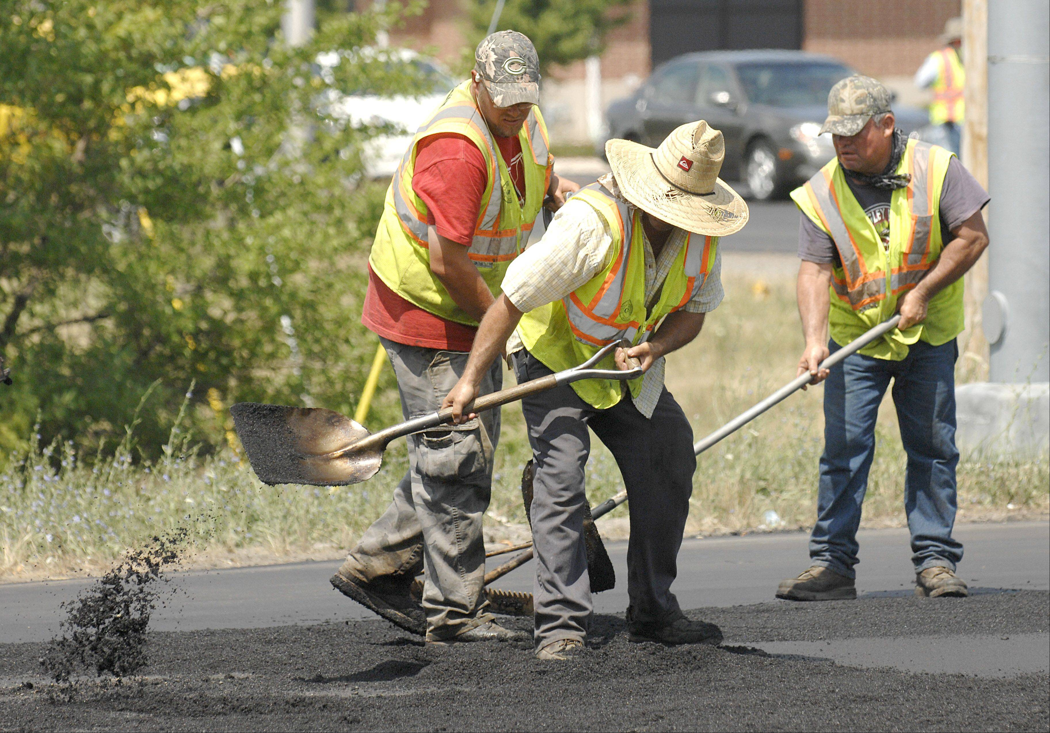 Workers with Curran Contracting Company of Crystal Lake spread hot asphalt at the intersection of Routes 38 and 47 in Elburn on Tuesday.