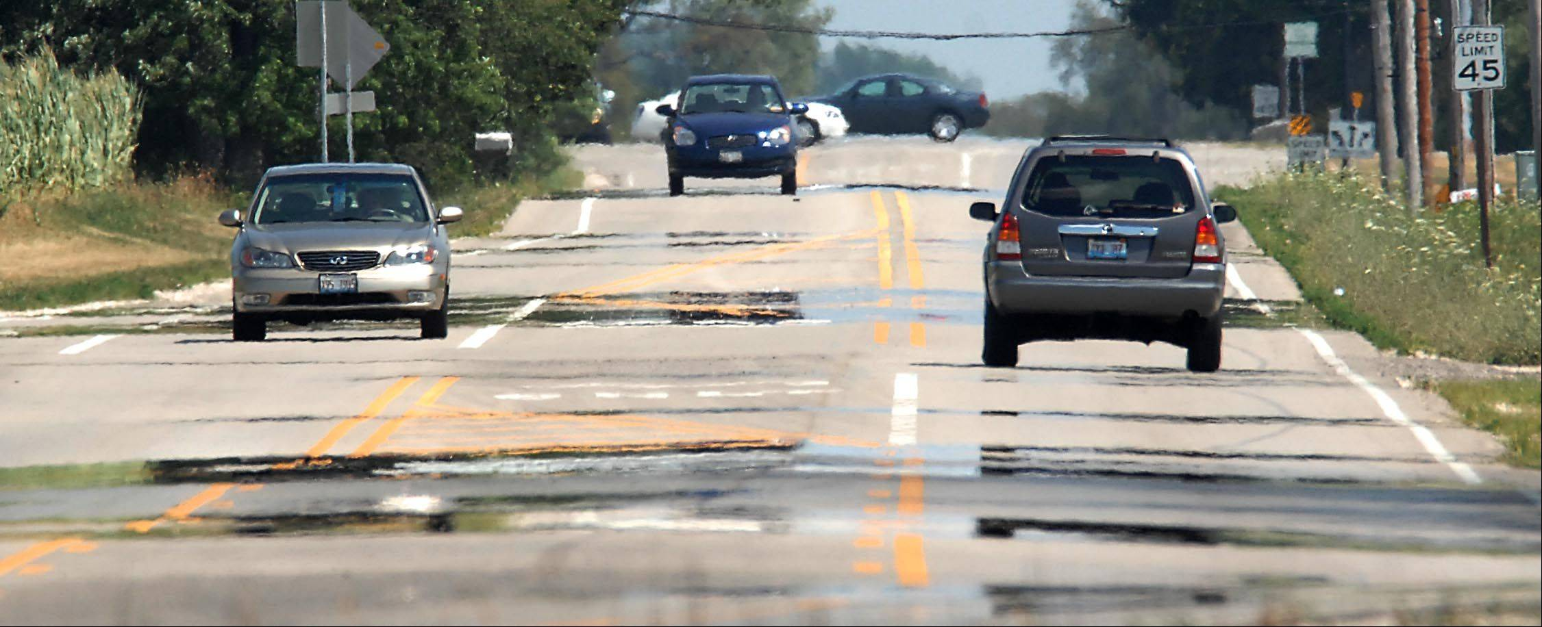 Heat waves form a mirage of puddles on the pavement along Huntley Road near Huntley Tuesday afternoon.