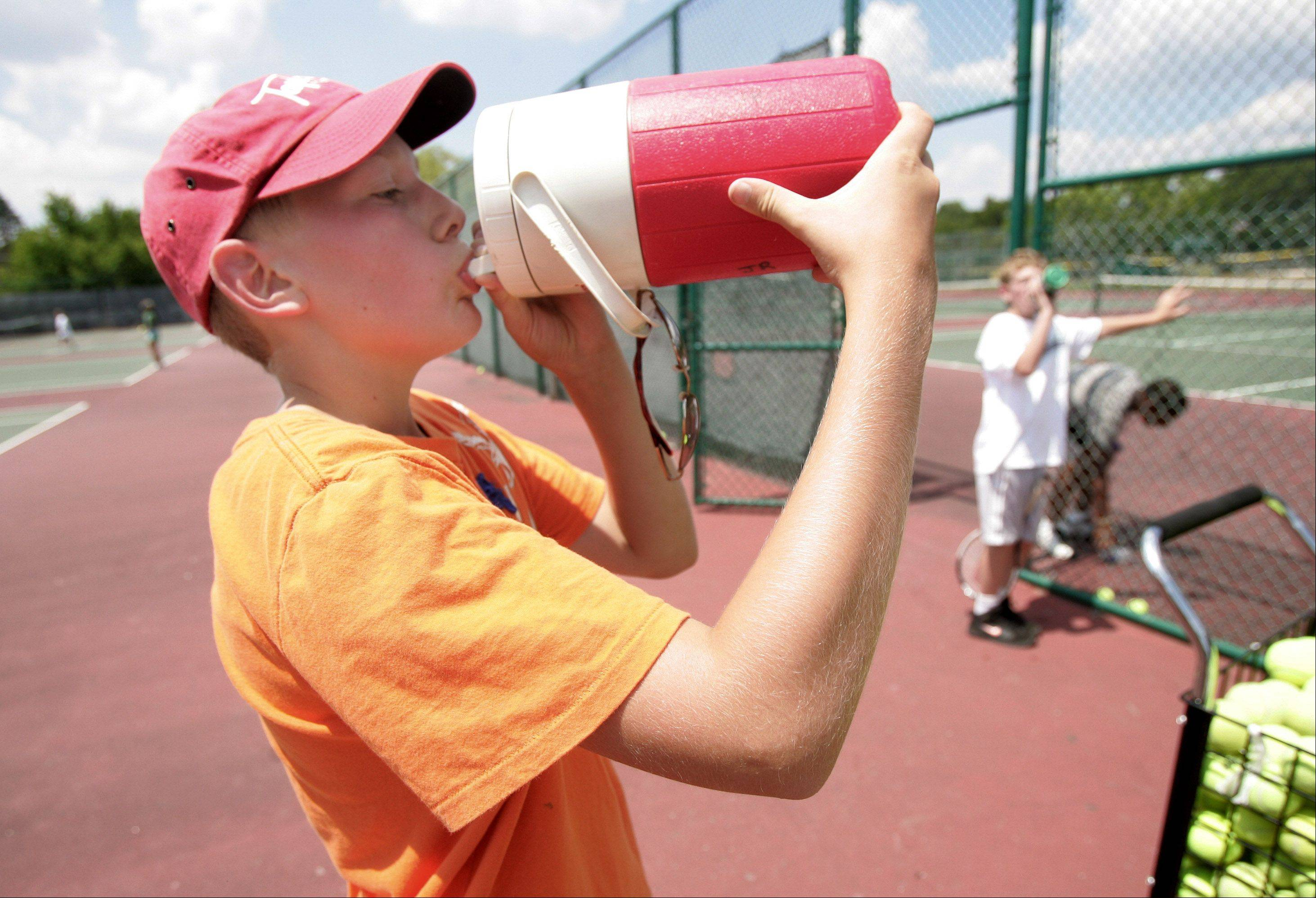 Jake Ryan, 11, of Round Lake, stops to drink water after playing tennis at Grayslake High School's summer tennis camp Tuesday.