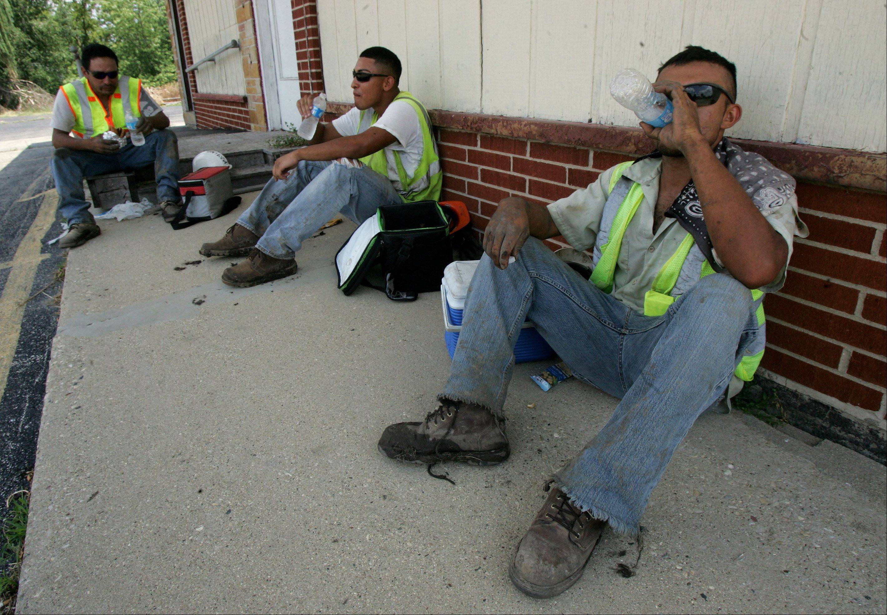 Laborers Diego Martinez, right, Margatio Jimenez, and Luis Salas, of Winters Landscaping, rest in the shade after planting trees along Rollins Road in Round Lake Beach Tuesday.