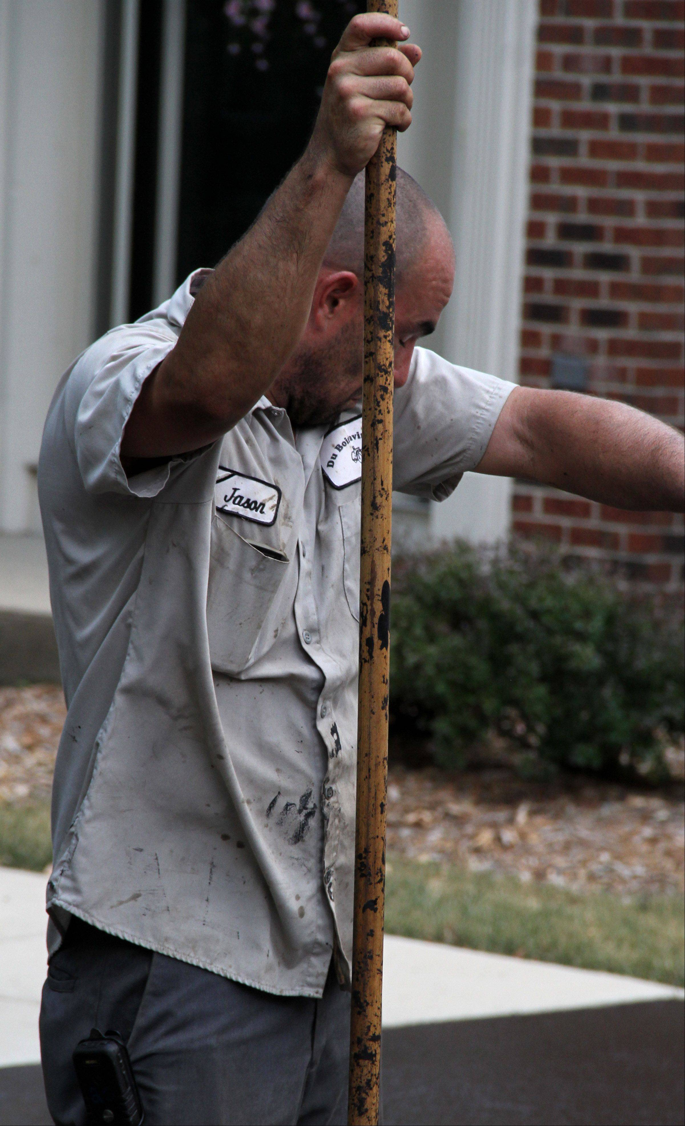 Jason Clem of Woodlawn wipes his forehead after applying sealer to condominium driveways in Wheeling on Tuesday.