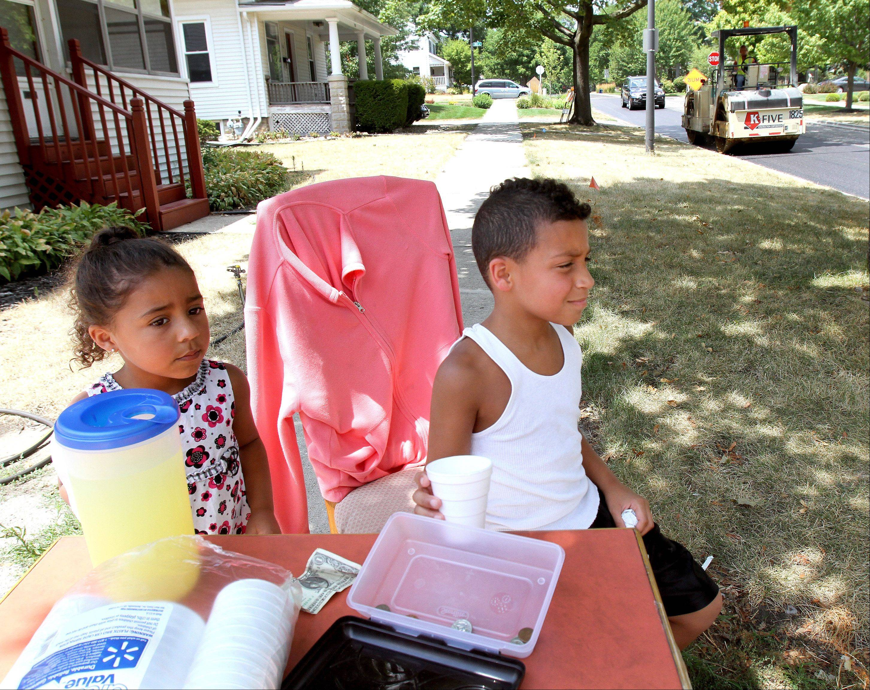 Laney Nelsom, 4 and her brother Bryan, 8, keep a lookout for potential customers at their lemonade stand in Naperville on Tuesday.