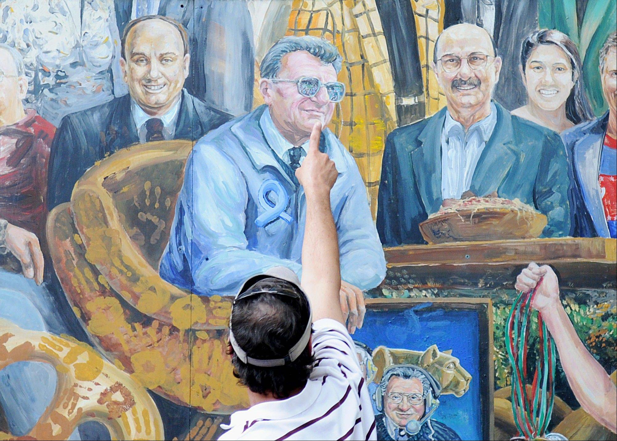 A visitor points to the spot in a mural by Michael Pilato where a halo that was above the late Penn State football coach Joe Paterno has been painted over by the artist in State College, Pa., Saturday.