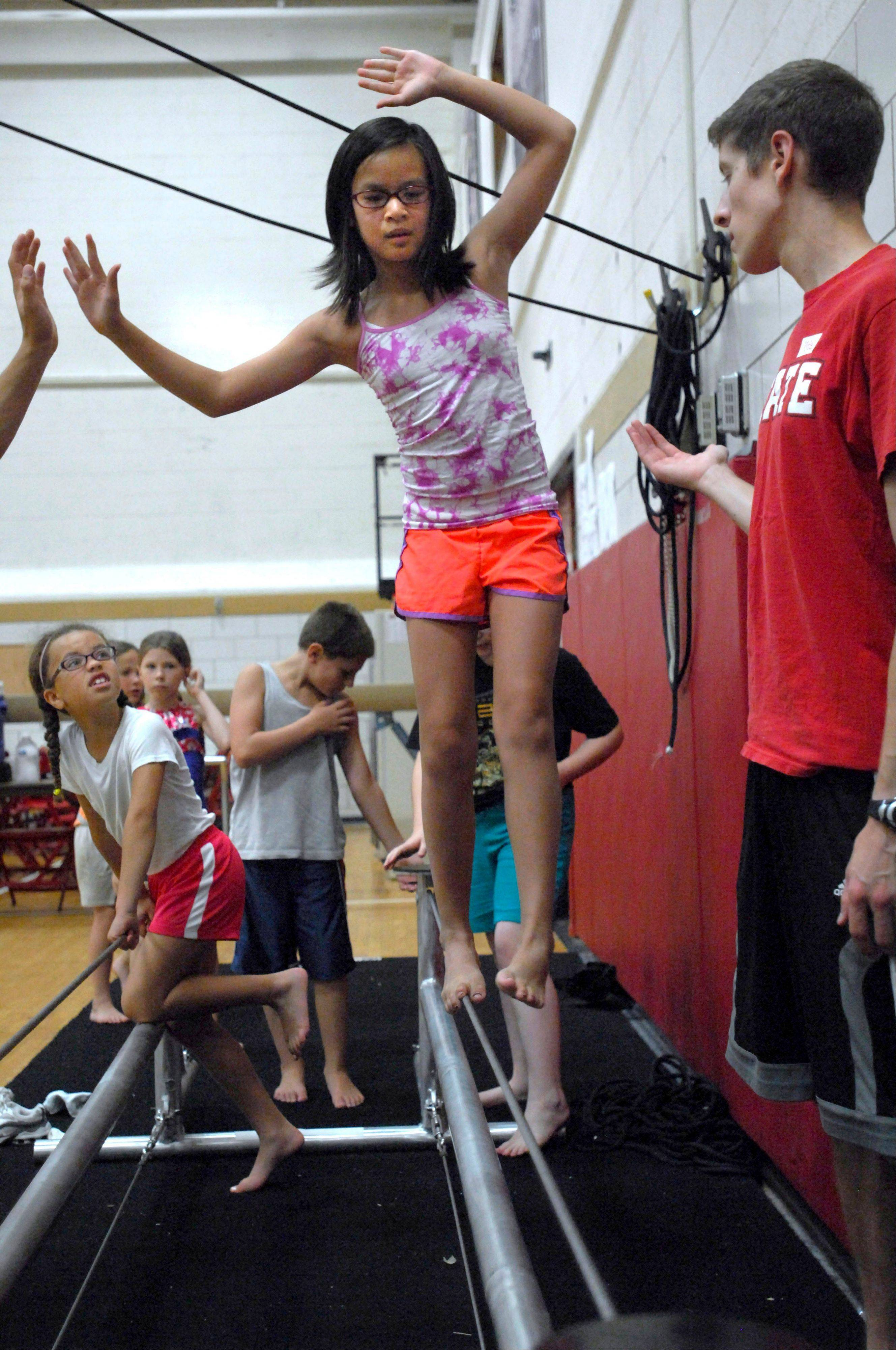Alex Seehuus, 12, of Hudson, Ill., walks a tightrope as Illinois State University senior Kyle Boyer helps her with her balance as she practices during circus camp at Horton Fieldhouse in Normal.