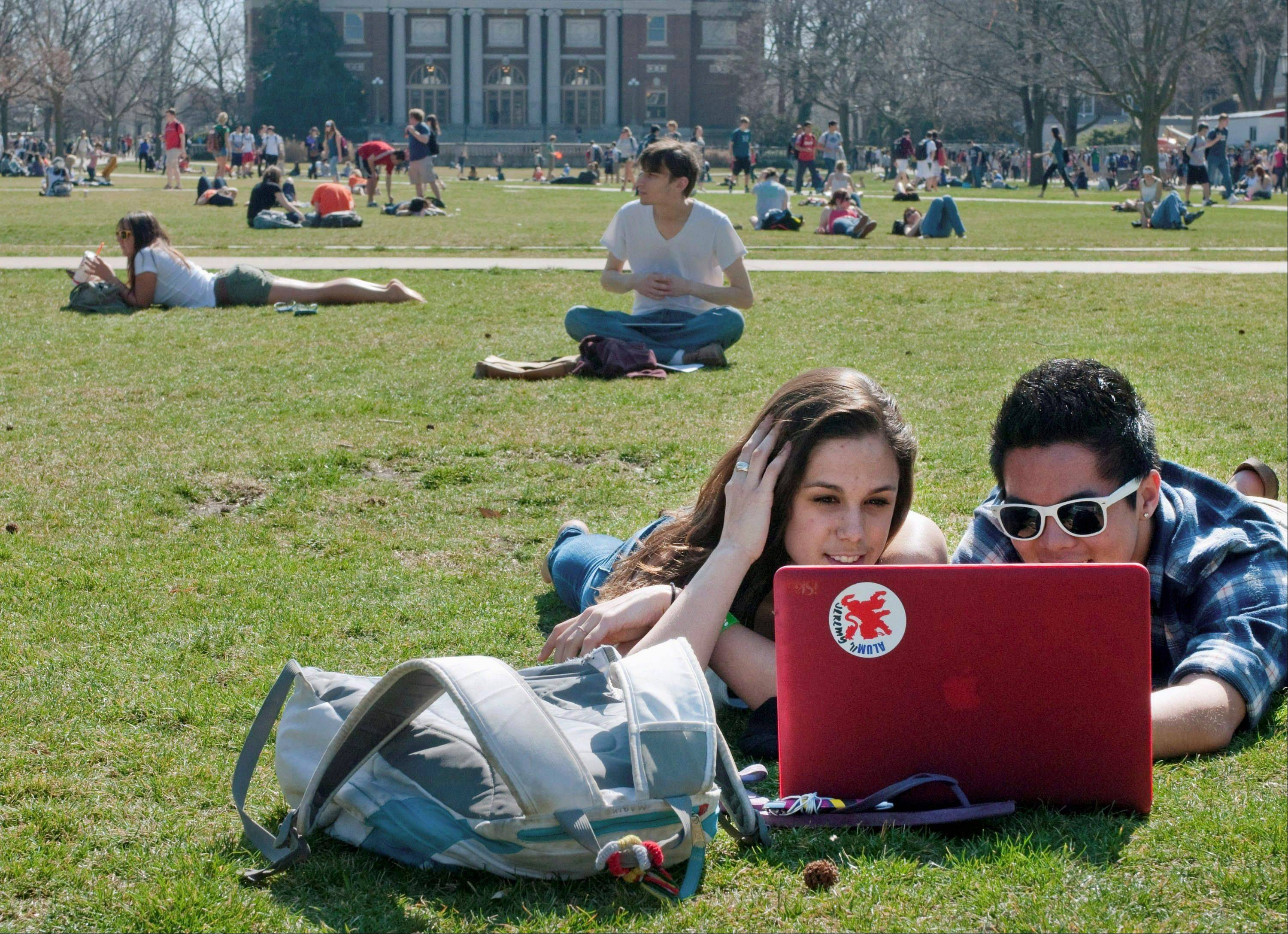 In this March 13, 2012 file photo, University of Illinois freshmen Jill Marik, left, and Jeremy Vivit study on the quad on campus in Urbana. The university plans to offer seven free online classes this fall.