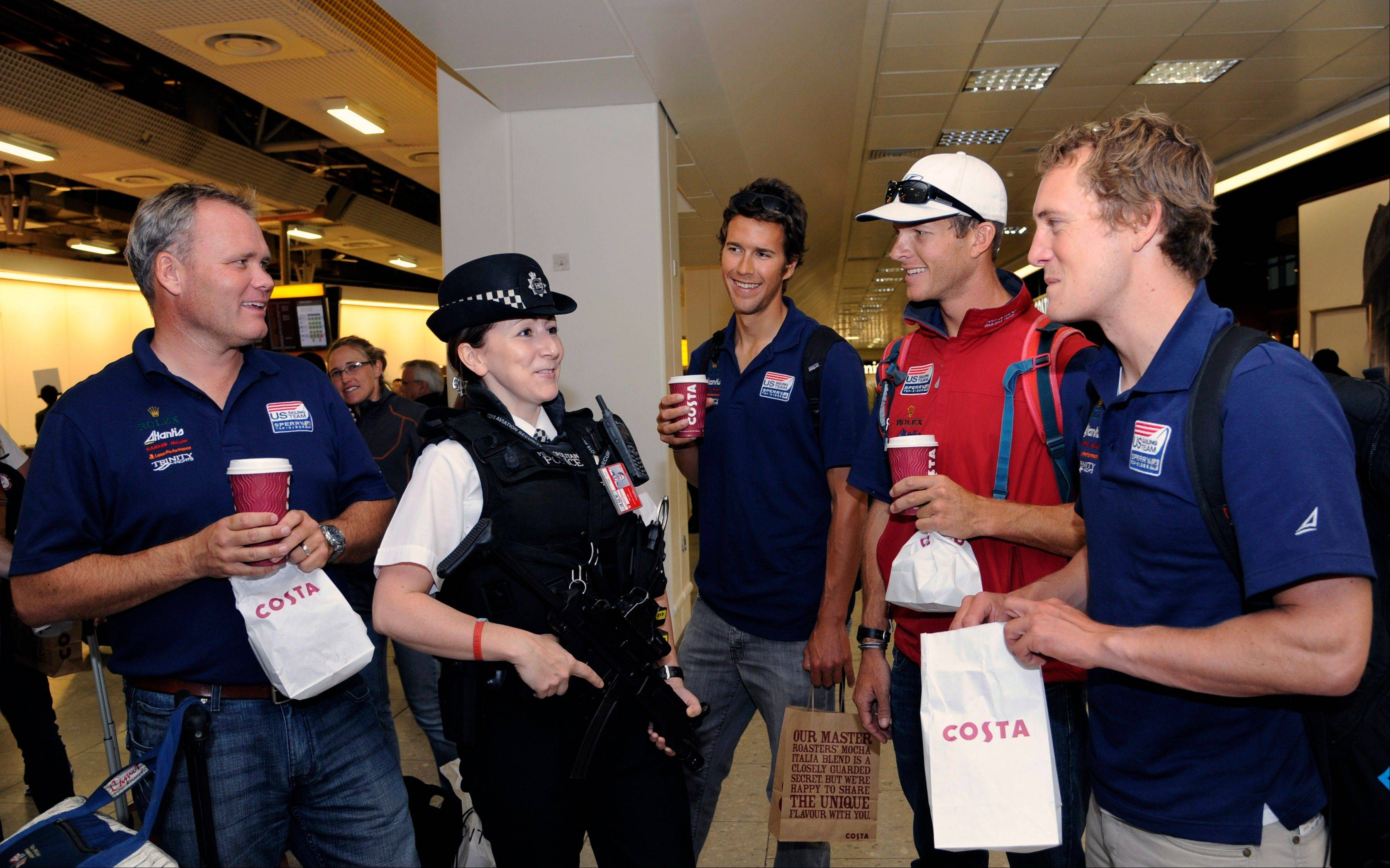 It's smooth sailing for these smiling members of the U.S. Olympic sailing team as they chat with a British police officer following their arrival at Heathrow Airport in London.