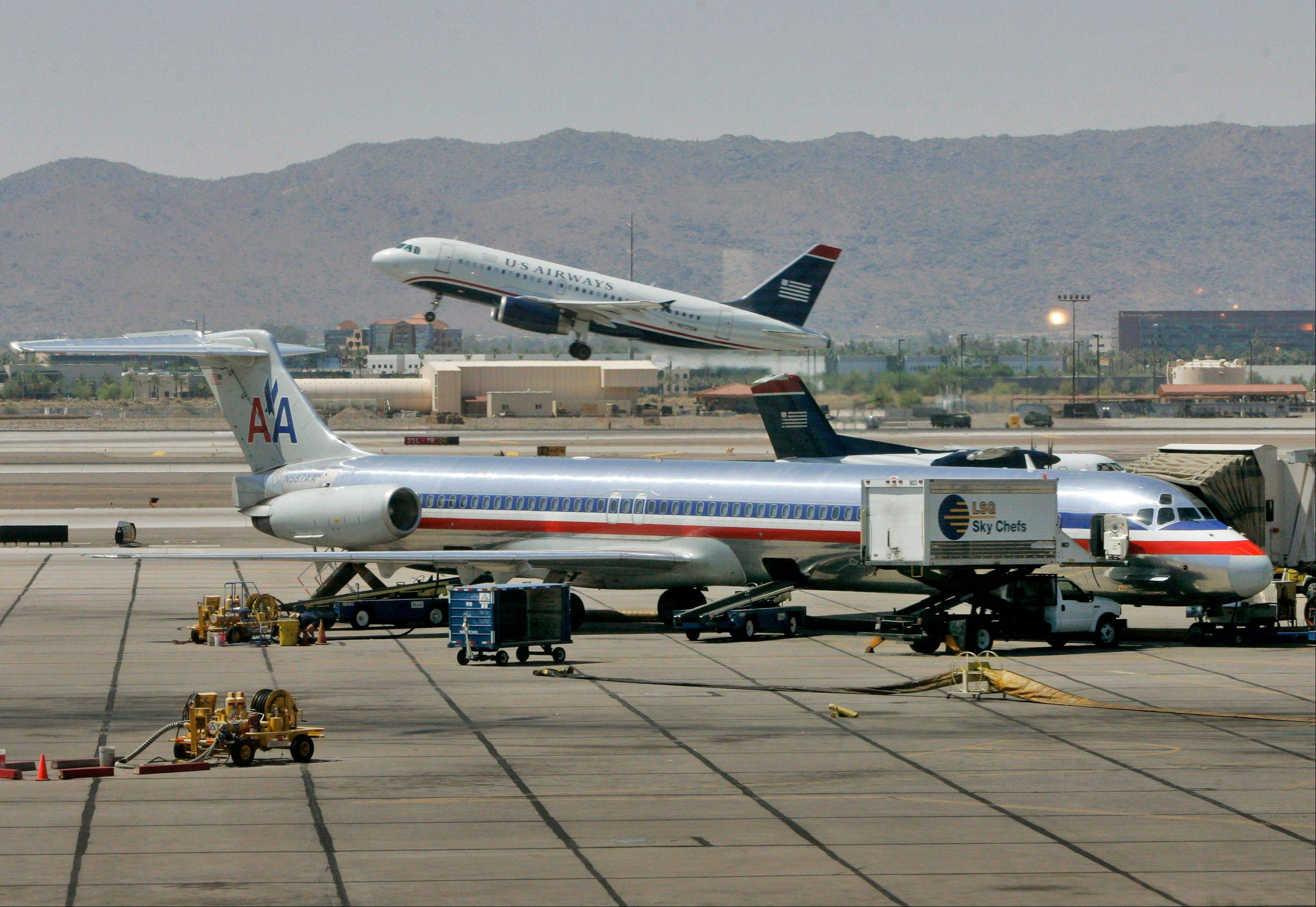 A US Airways jet takes off at Sky Harbor International Airport in Phoenix. US Airways' CEO is getting impatient over the possibile merger between his airlines and American Airlines.