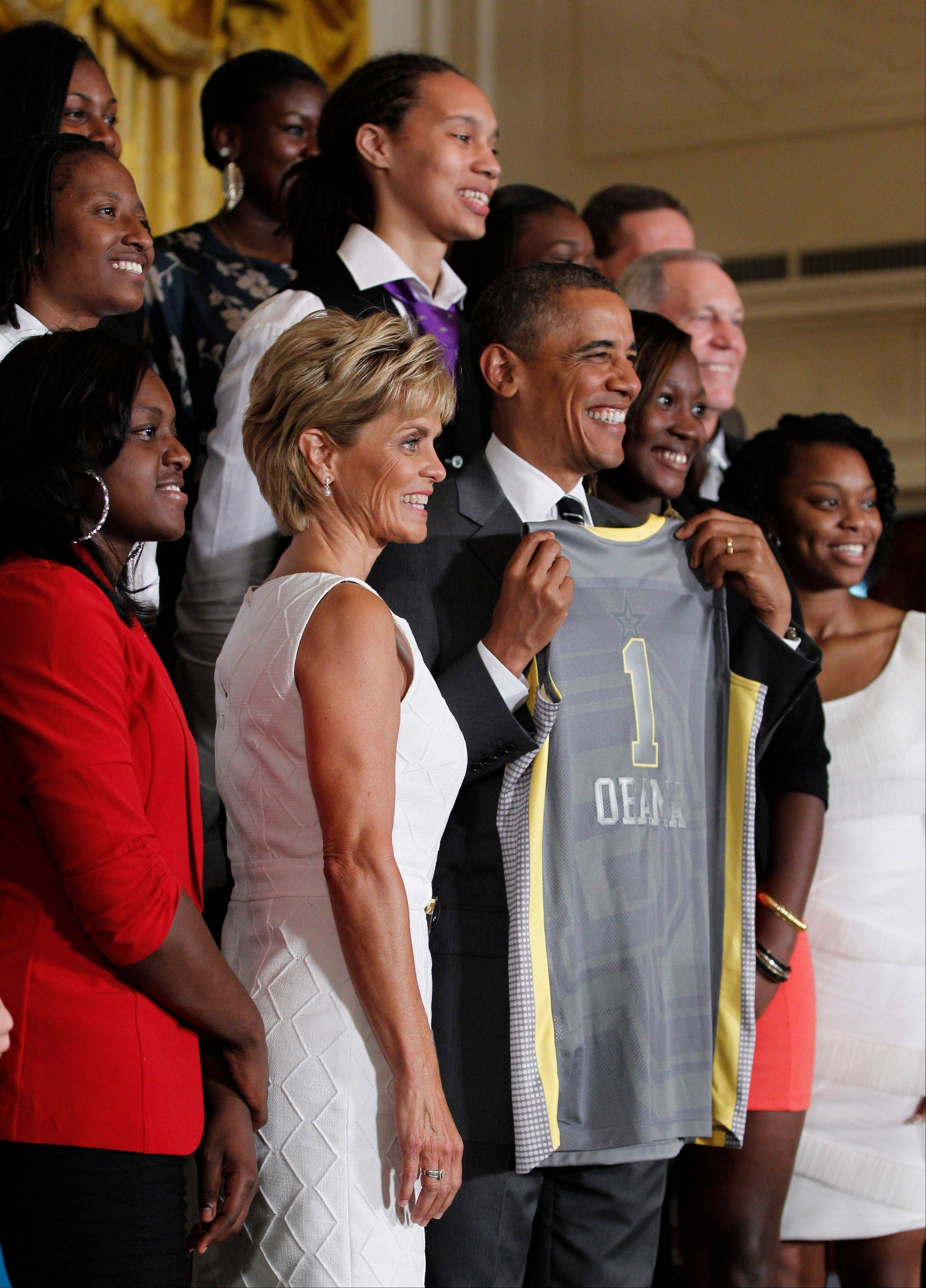 President Barack Obama, center, holds up a jersey given to him by members of the 2012 NCAA Women's basketball champion Baylor University Bears during a ceremony at the White House Wednesday.