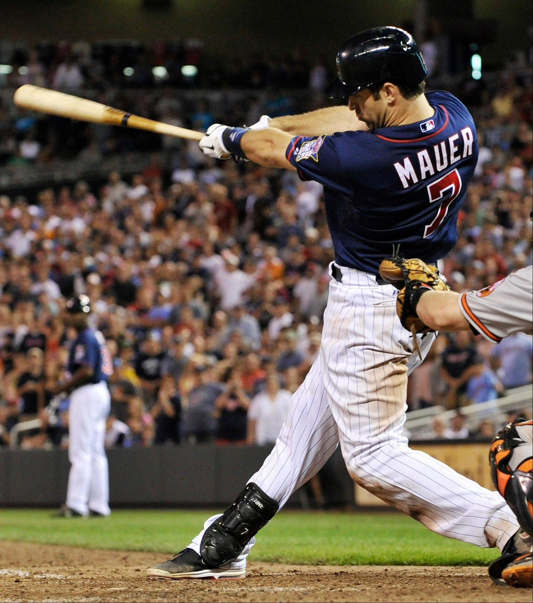 The Minnesota Twins' Joe Mauer hits an RBI single off Baltimore Orioles pitcher Pedro Strop Tuesday during the eighth inning in Minneapolis. Mauer went 3-for-4 as the Twins won 6-4.