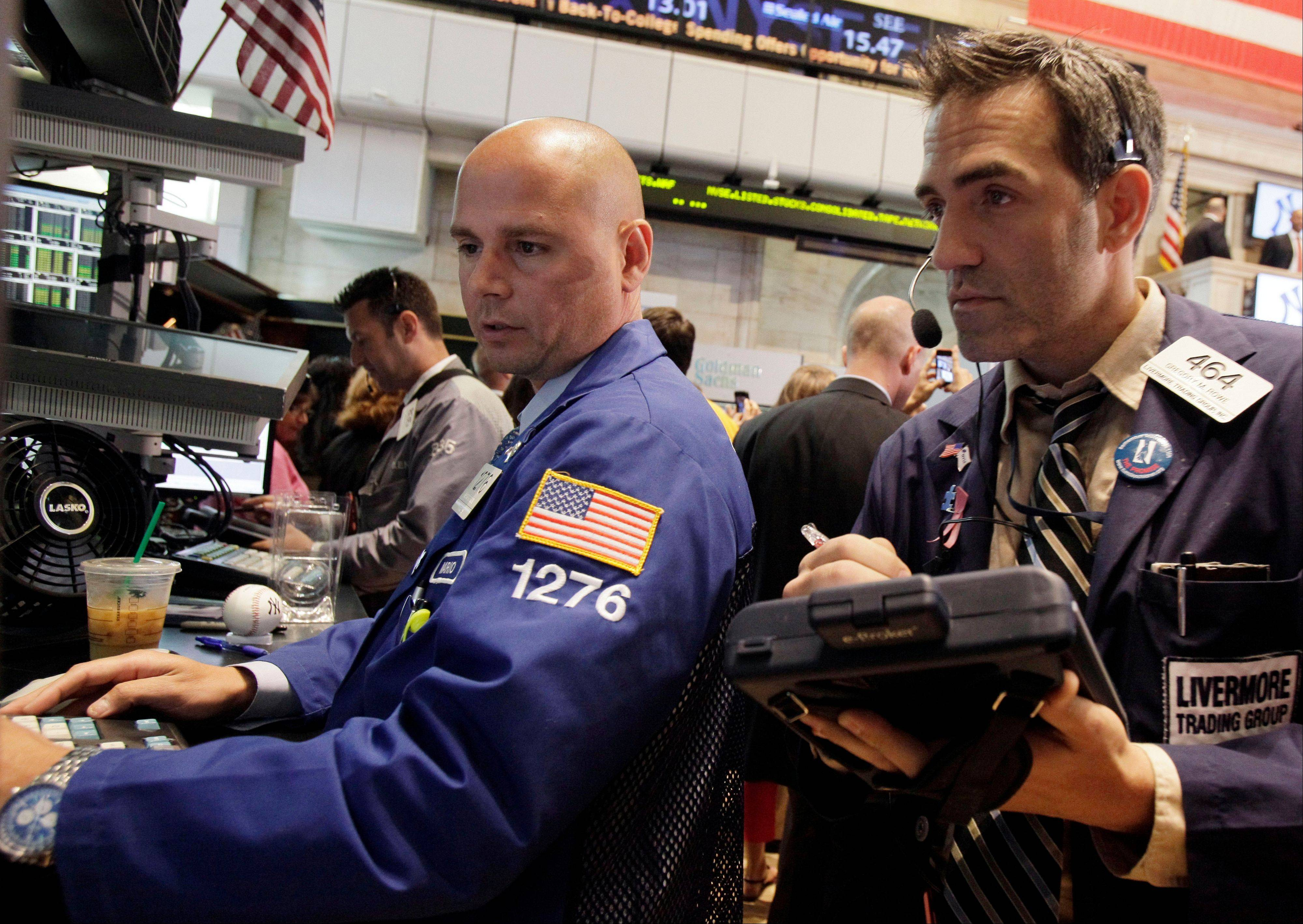 Specialist Mario Picone, left, and trader Gregory Rowe work on the floor of the New York Stock Exchange Wednesday, July 18, 2012. U.S. Stocks rose in early trading Wednesday as investors weighed new signs of a housing rebound against weak earnings reports from several big companies.