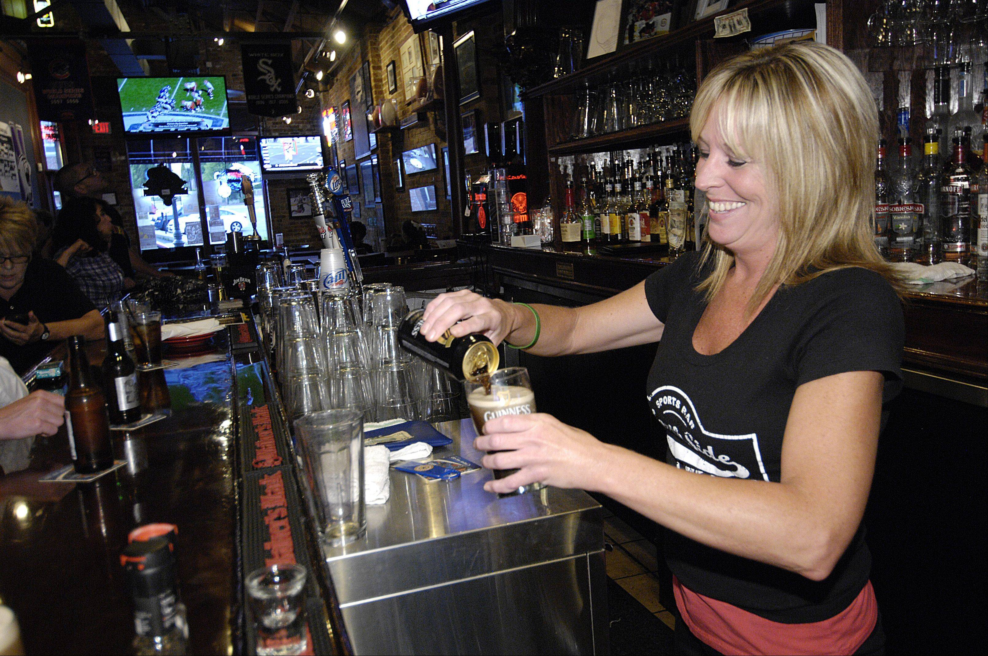 Heather Murphy pours a Guinness for a customer at the North Side Sports Bar & Grill in Glen Ellyn.