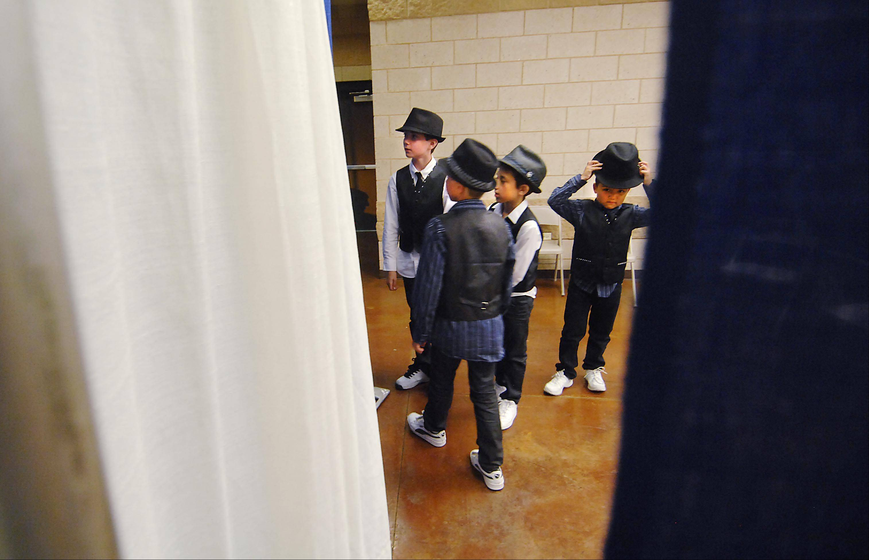 "Ethan Reimer, Dominic Campobasso, and Ian Berk watch the stage as Isaac Serna adjusts his hat while they wait backstage just before their turn Monday night at the 29th Annual Kane County Fair Talent Contest in the Prairie Events Center at the fairgrounds in St. Charles. The Aurora pre-teen group performed a Hip Hop Dance called ""Bounce""."