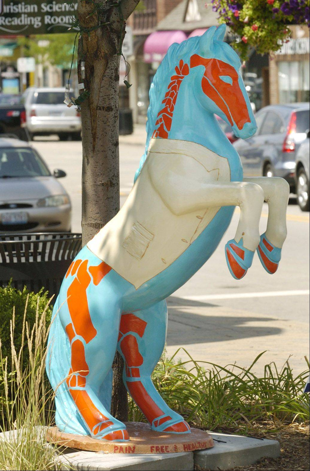 "Decorated ceramic horses are on display throughout Barrington for a Barrington Area United Way fundraiser. This one, in front of the Bread Basket Restaurant, called ""Free to Delight"" by artist Kristin Prunskis is sponsored by Hart Road Pain and Spine Institute."