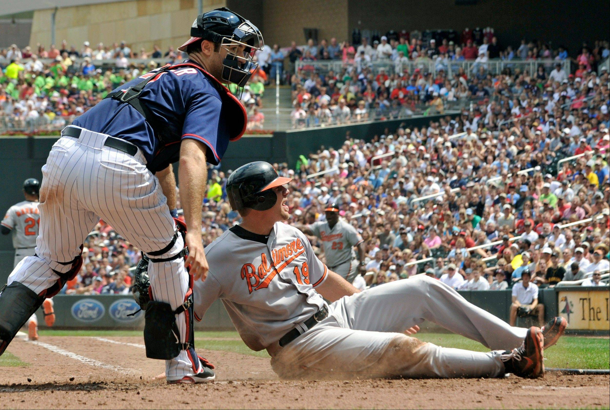 The Baltimore Orioles� Chris Davis looks for the call as he slides in to score on Minnesota Twins catcher Joe Mauer, left, after third baseman Trevor Plouffe�s throwing error Thursday during the seventh inning in Minneapolis.