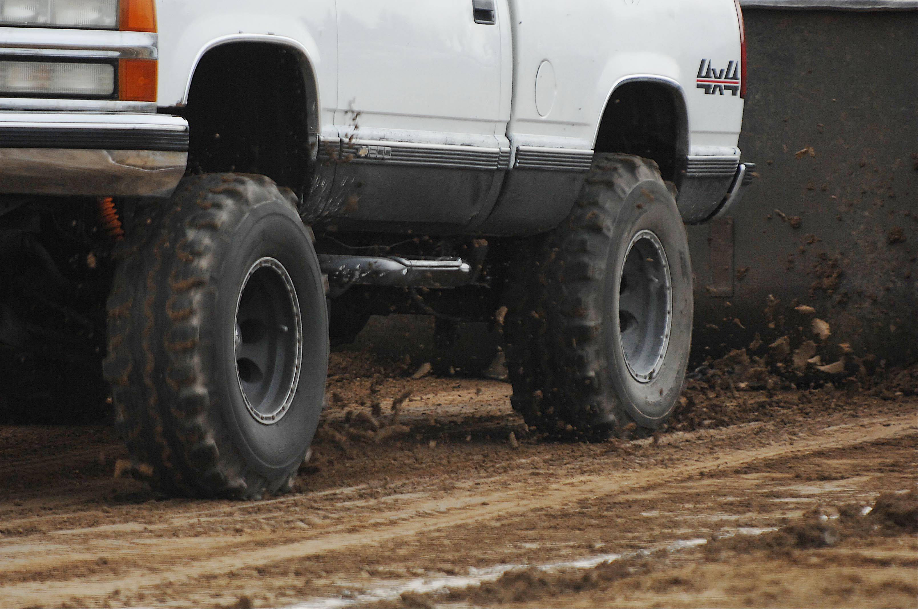 Mud and dirt is churned up from the tires of a pickup truck during a truck pull competition at the Kane County Fair Thursday in St. Charles.