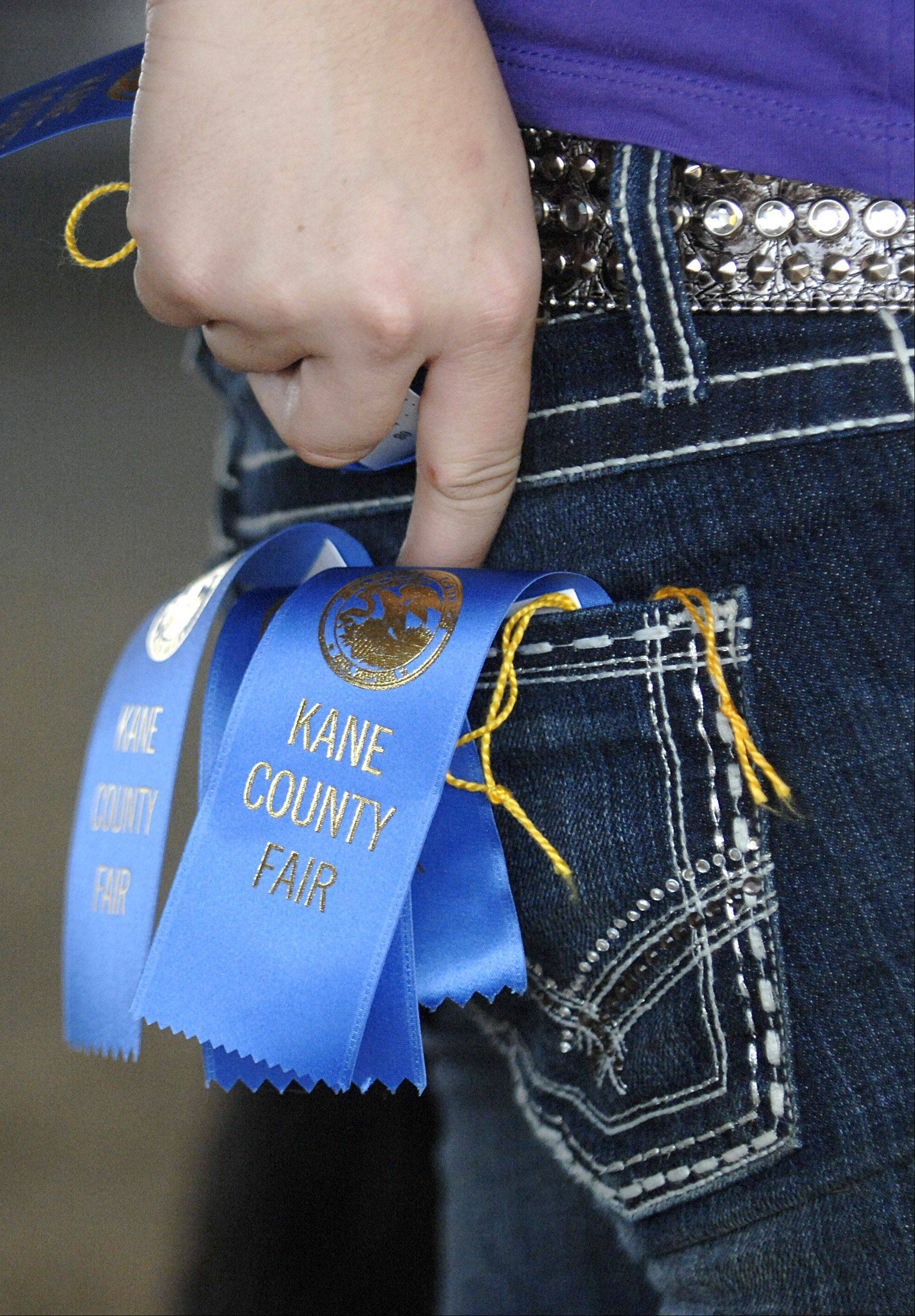 Brittani Koning of Pecatonia shoves another first place ribbon for her sheep in her back pocket during the second day of the Kane County Fair on Thursday.