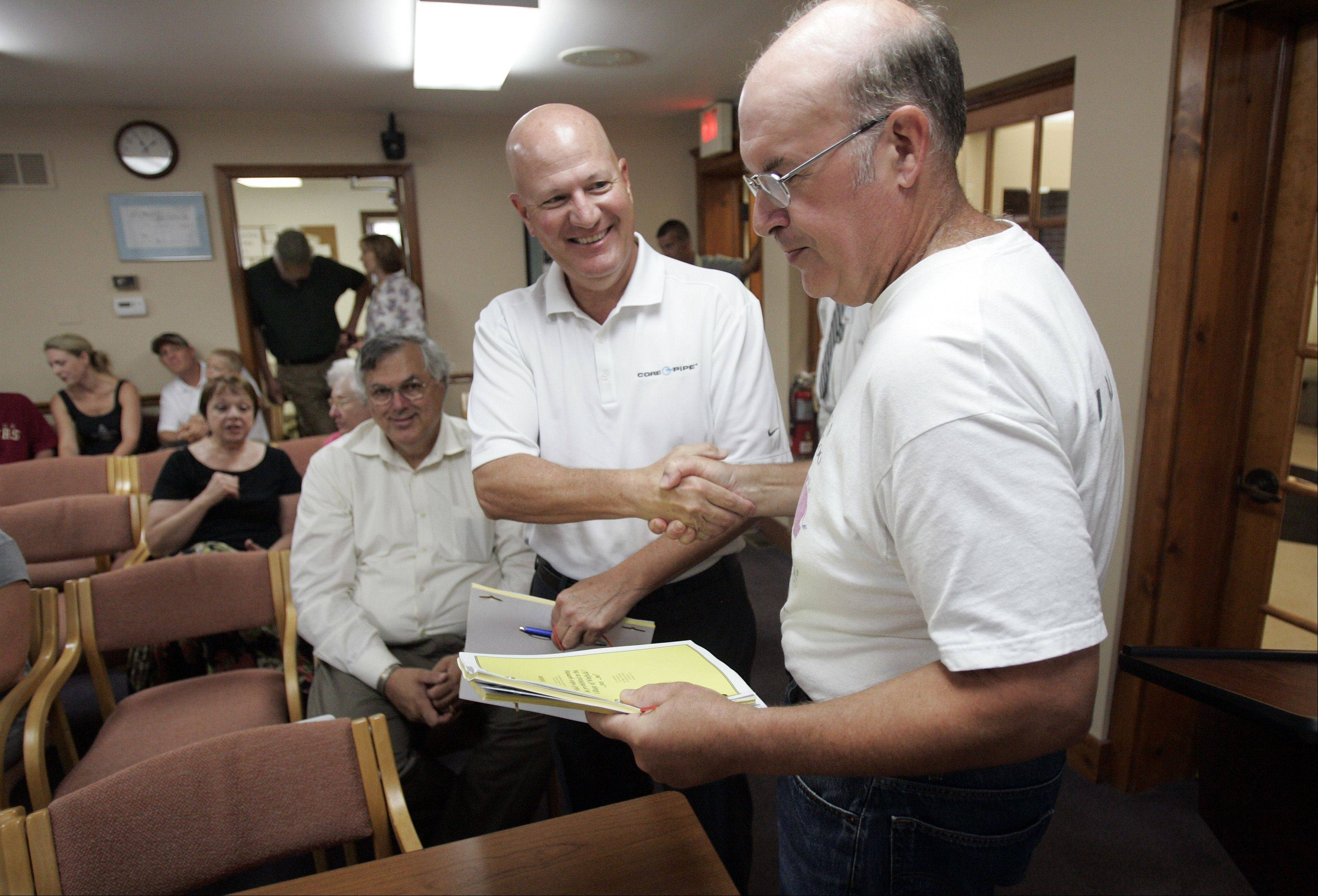 Winfield residents Steve Romanelli, left, and Harold Besch congratulate each other after submitting petitions calling for a referendum in November on video gambling and keeping the local police department intact.
