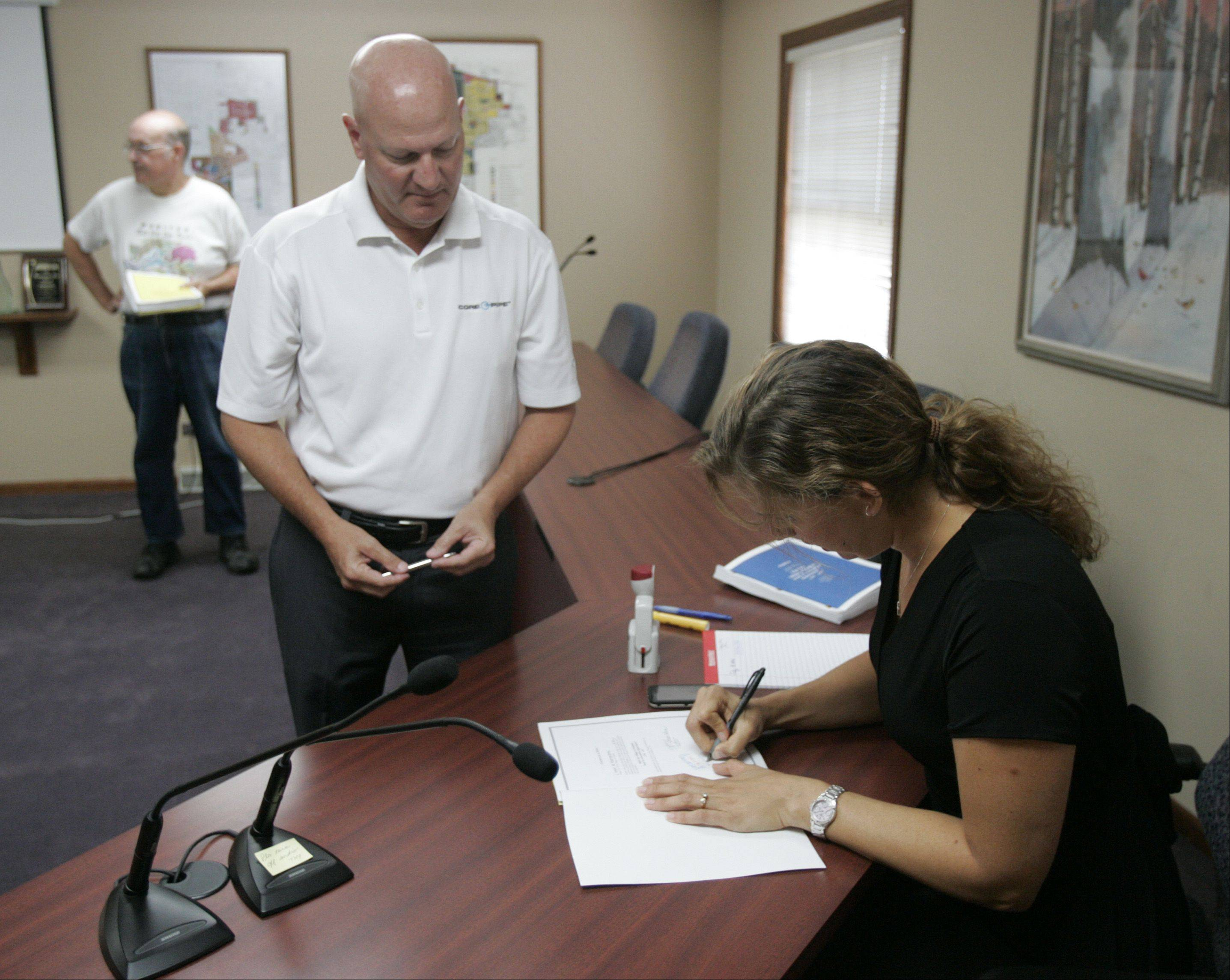 Winfield resident Steve Romanelli gives a petition Wednesday to Village Clerk Anne Mareachen at village hall calling for two questions to be put on the November ballot.