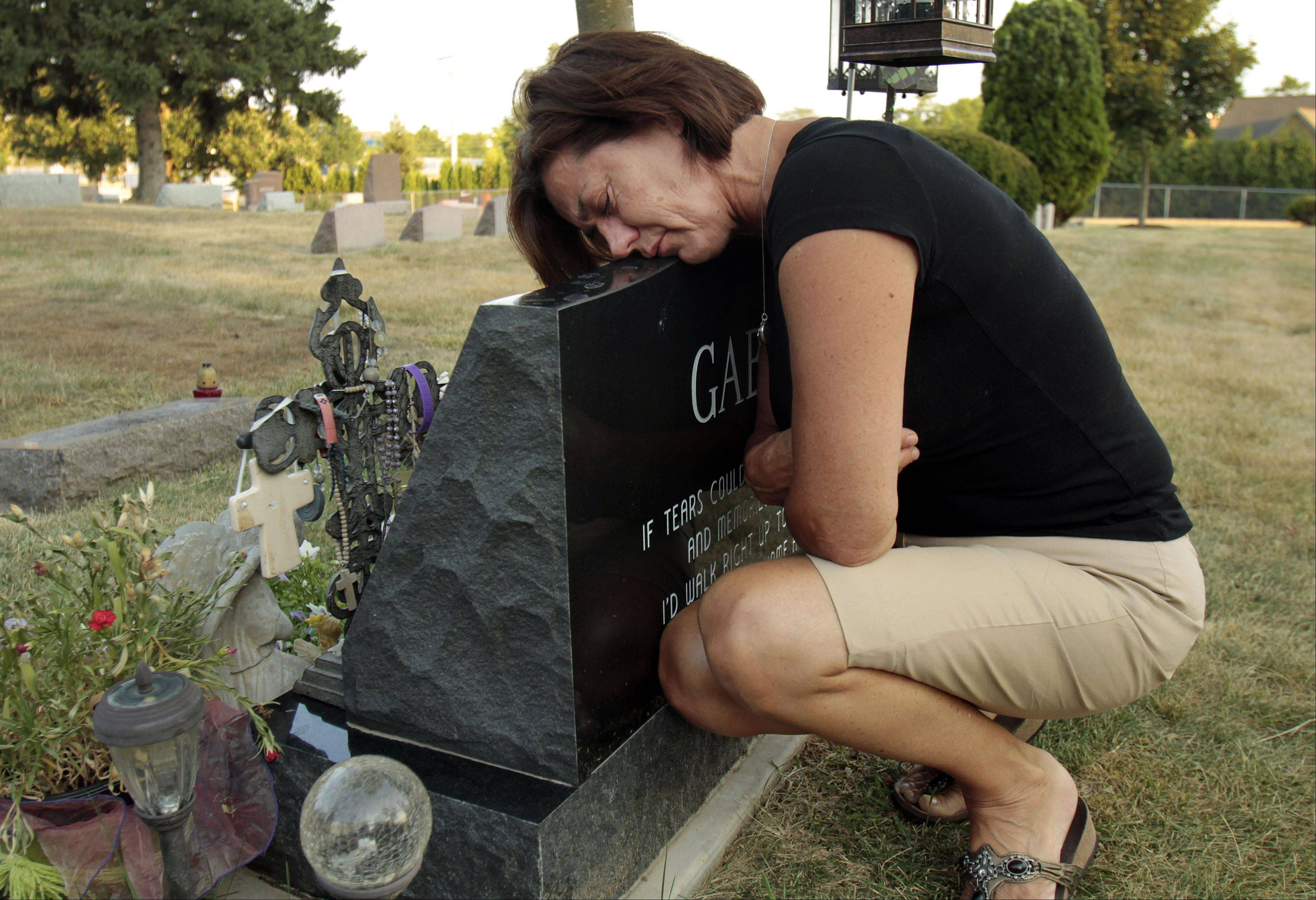Teresa Drozdz of Lake Zurich rests her head on the headstone of her daughter, Gabriella Drozdz. Gabriella died a year ago when she was struck by a hit-and-run driver while walking along Church Street in Lake Zurich.