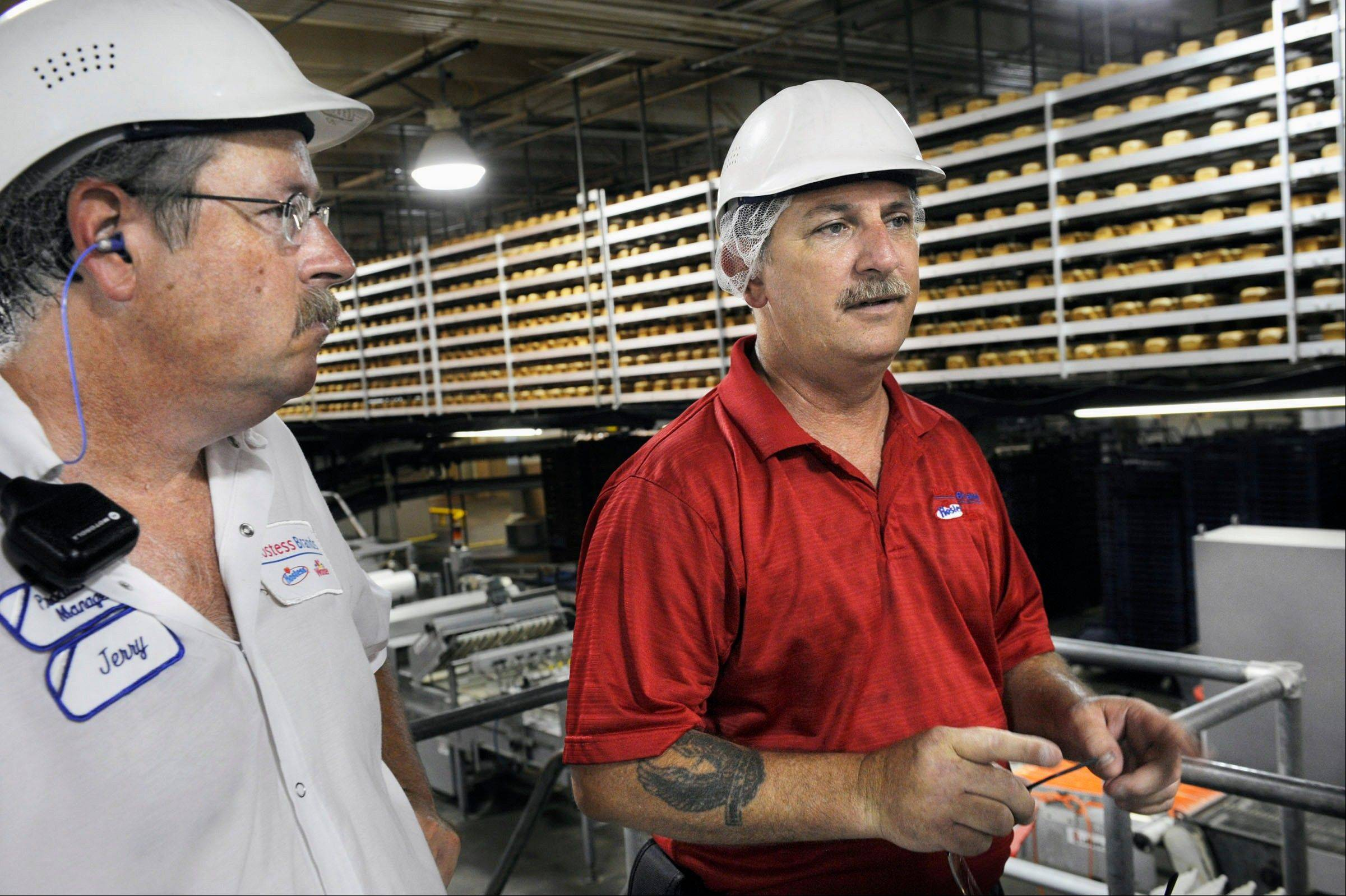 General manager Matt Stringer, right, and operations manager Jerry Montgomery talk about the Butternut bread plant in Peoria as thousands of loaves of bread pass by on the cooling racks in the background. The bakery has been in Peoria since the 1890s originally as Shulze's Buttercrust Bakery.