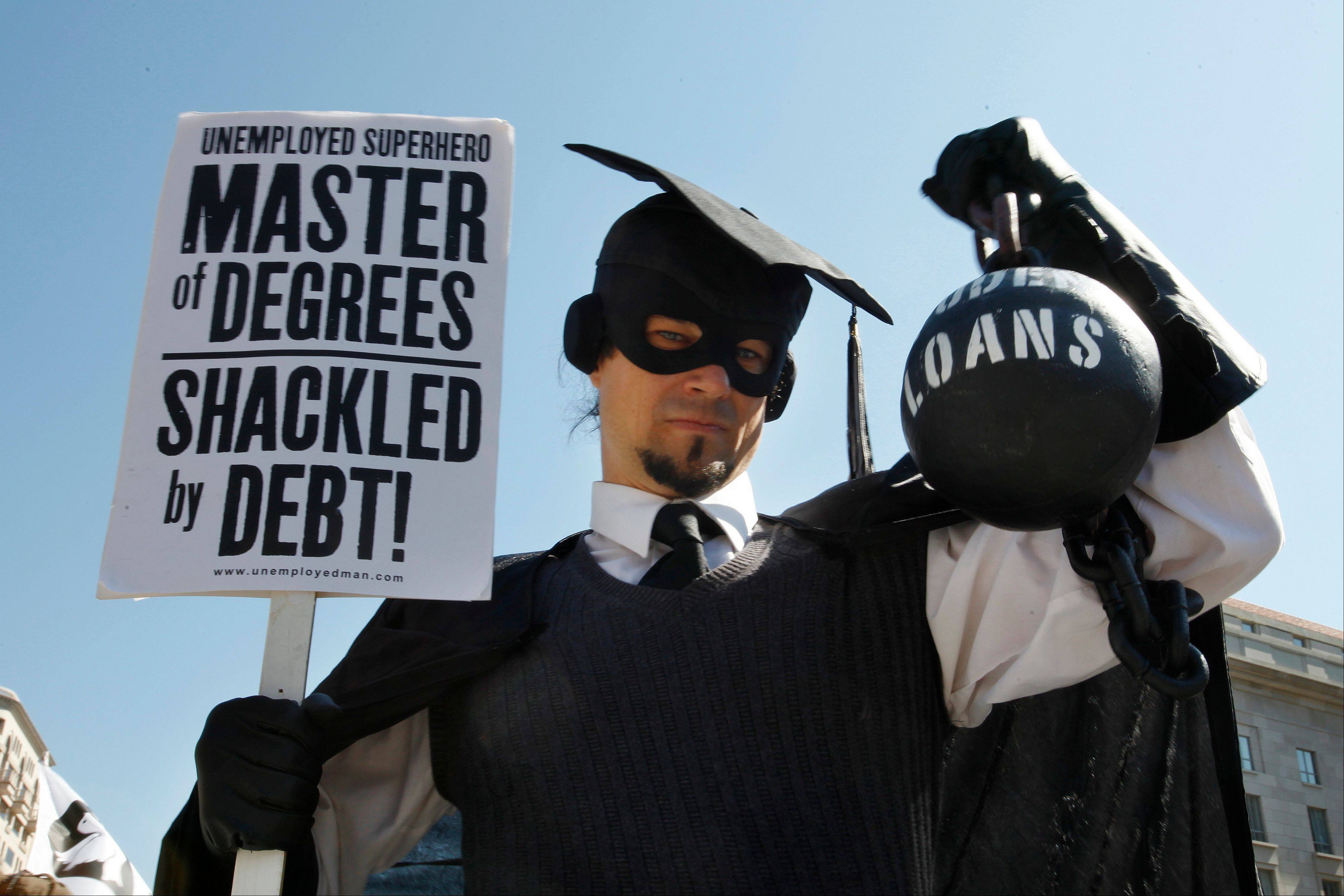 Gan Golan, of Los Angeles, dressed as the �Master of Degrees,� holds a ball and chain representing his college loan debt, during Occupy DC activities in Washington.